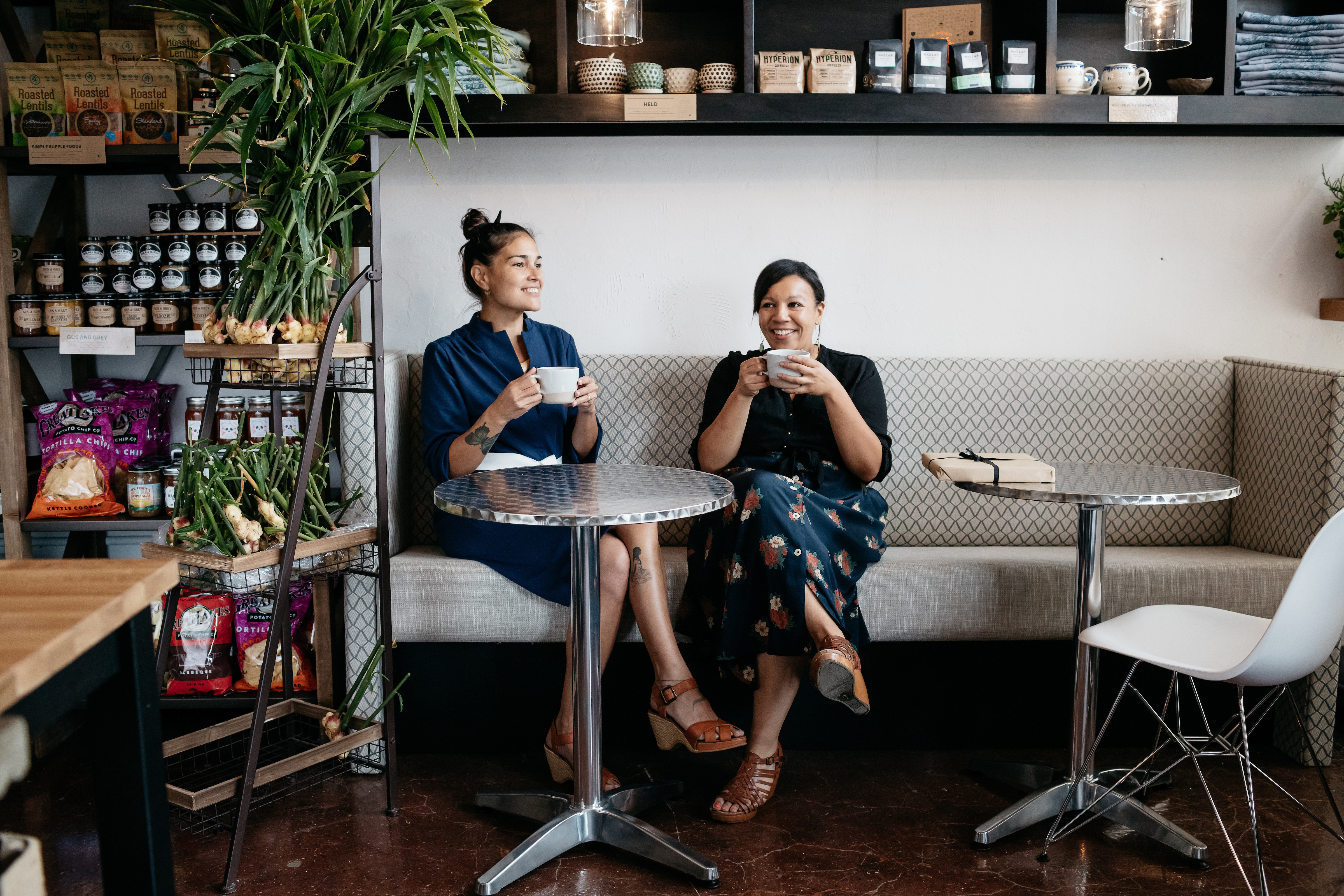 Both women are sitting at a table with mugs of coffee.