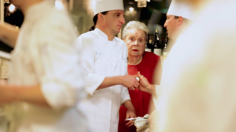 Ella Brennan and chefs in a restaurant kitchen