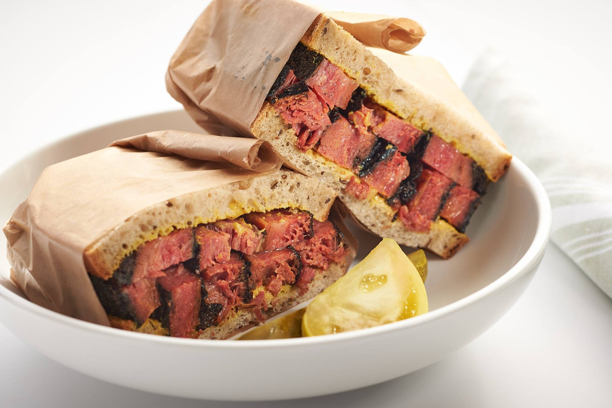 Thick cut pastrami on rye bread, wrapped in brown paper and served on a white plate on a white background.