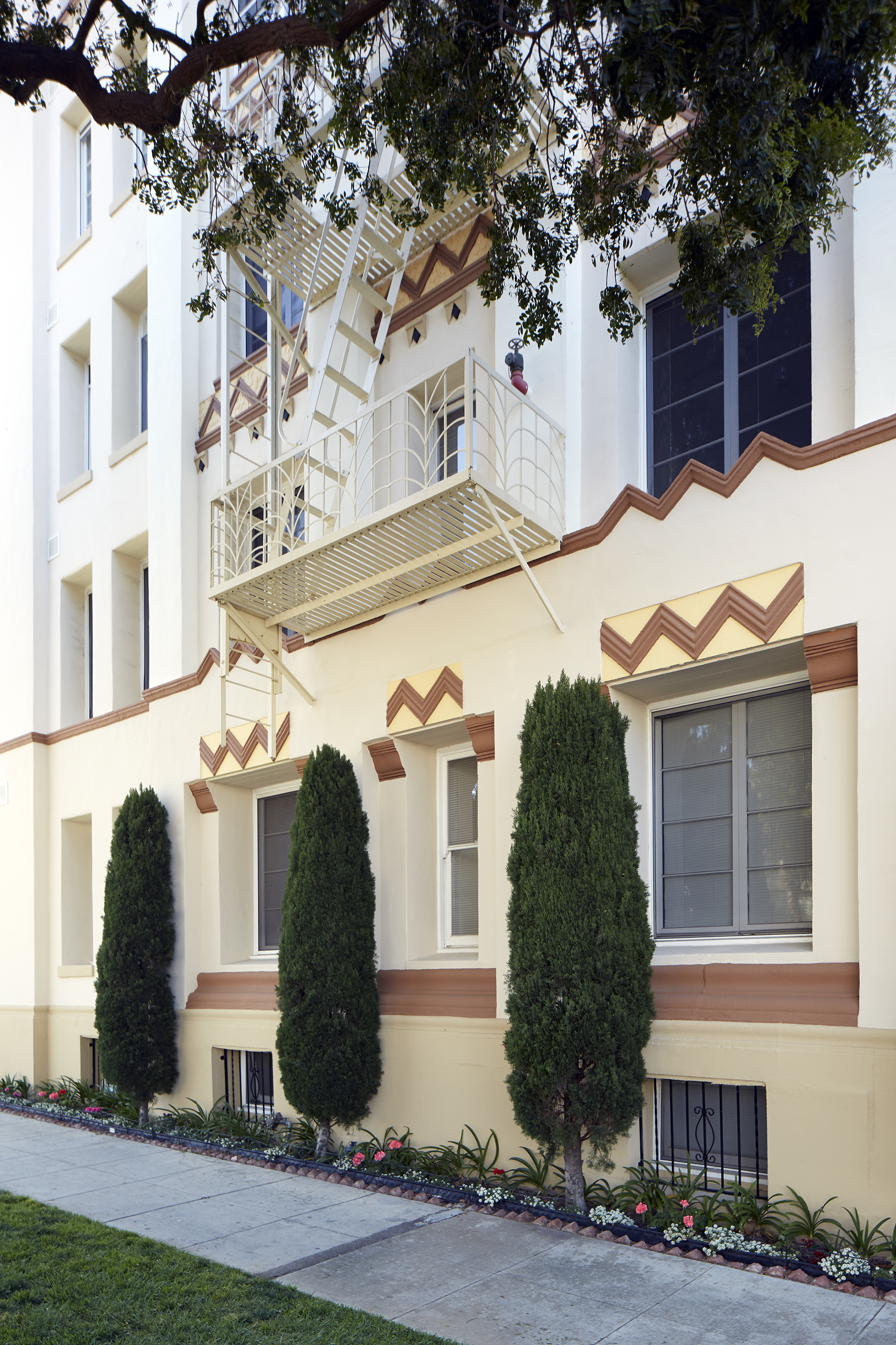 An older apartment building in pristine shape. It's painted in various shades of cream with a brown zig zag motif and a fire escape painted white. Three manicured juniper bushes front the building.