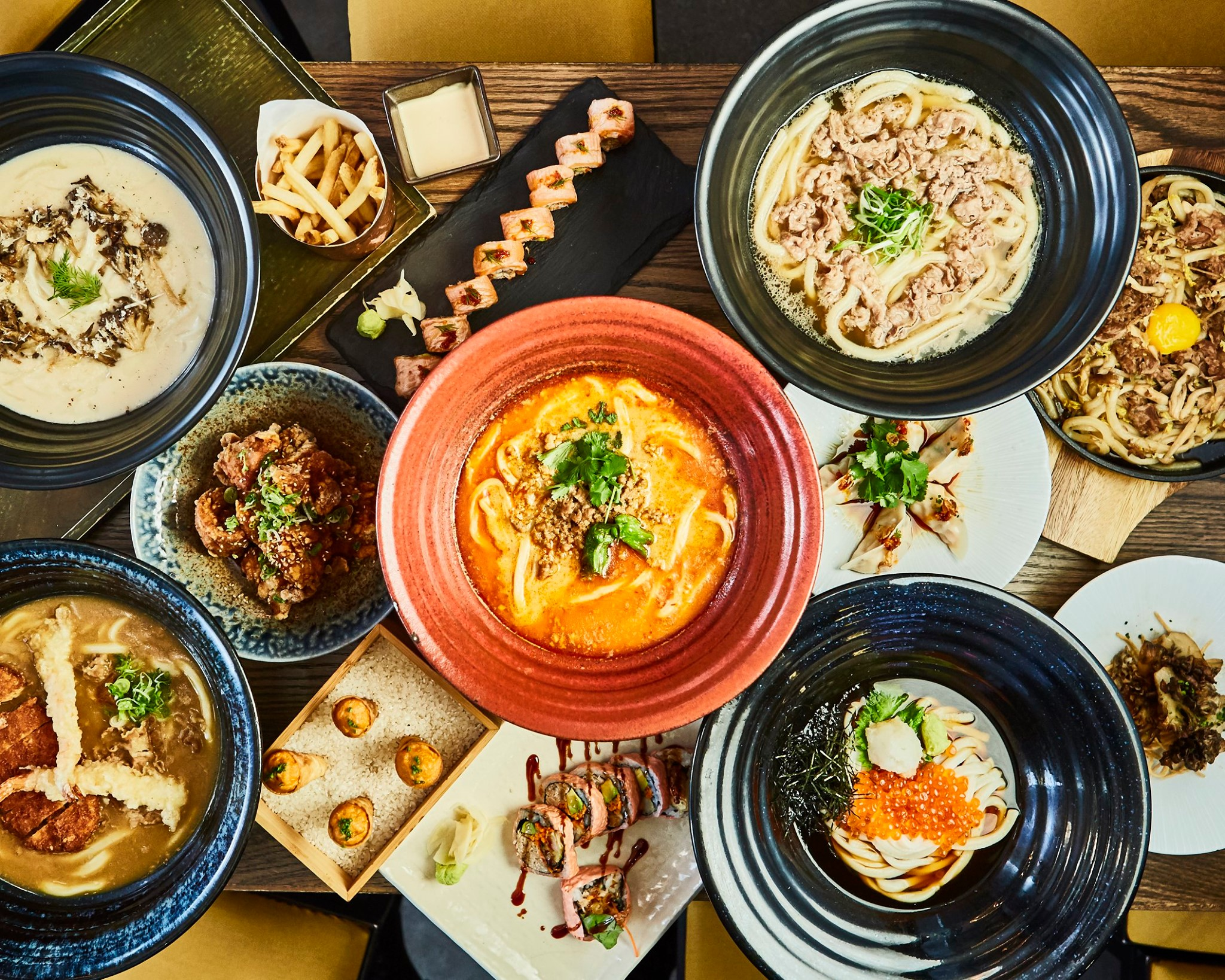 A table full of dishes, including multiple noodle soups, maki rolls, gyoza, and uni appetizers