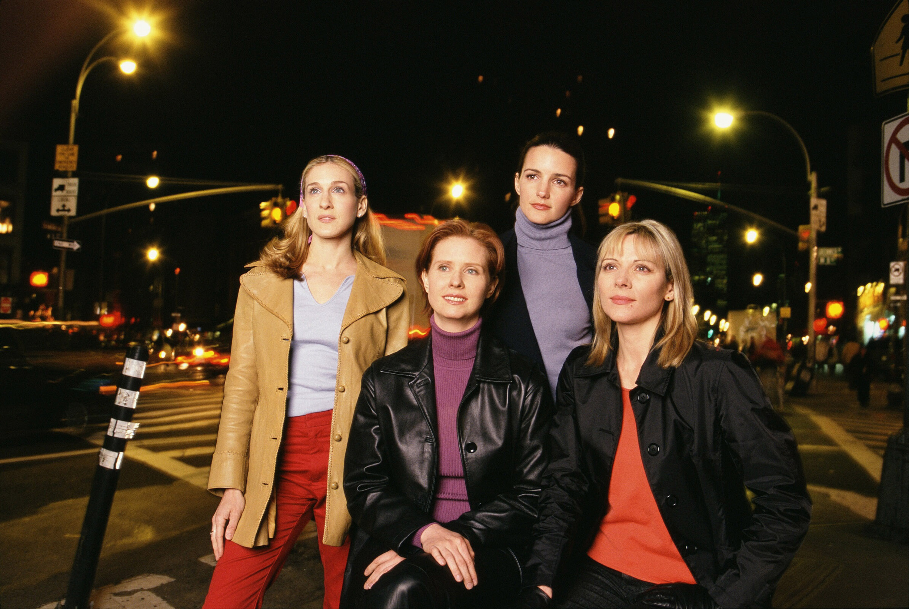 Four women pose for a camera. In the background is a city intersection at night.