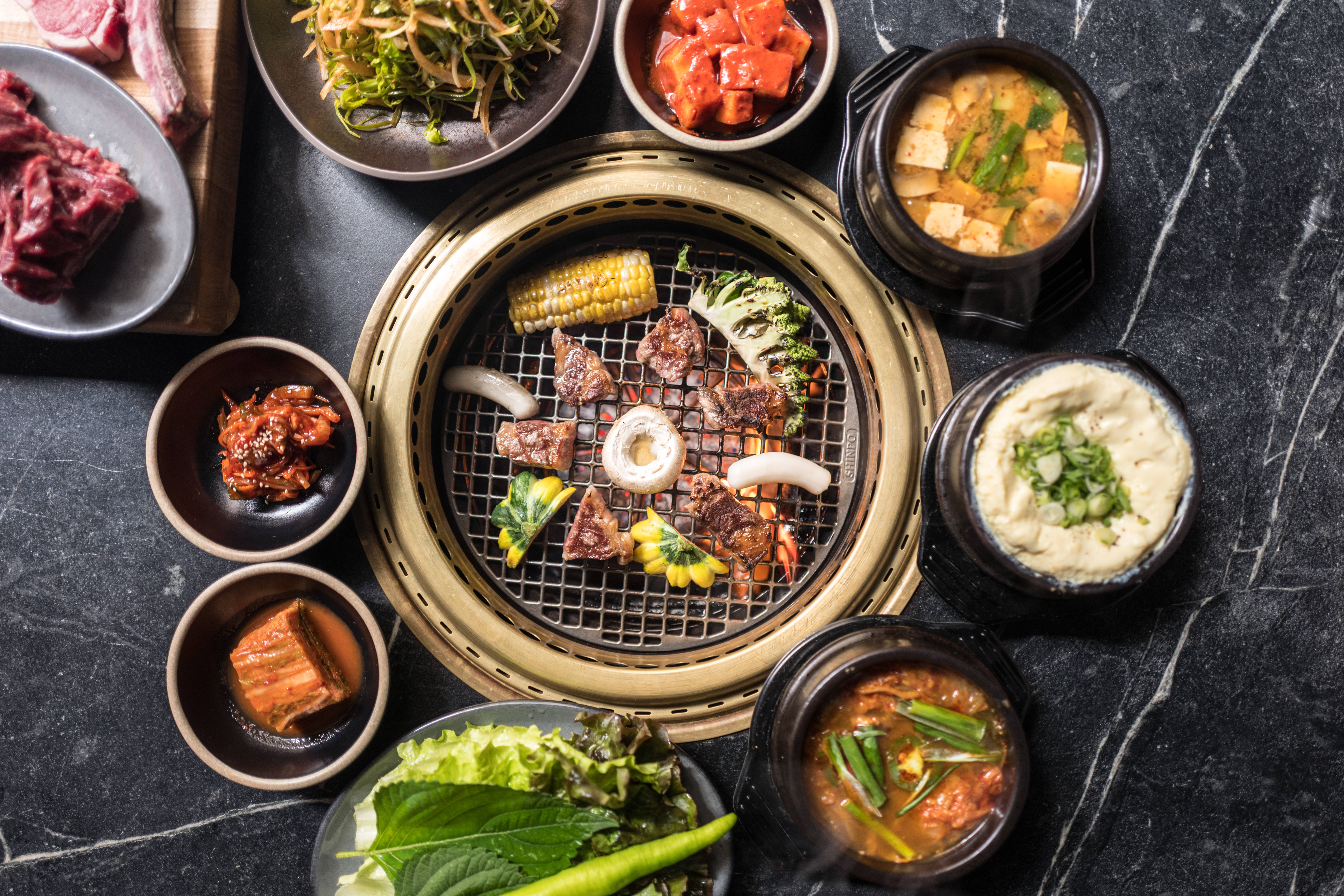 A circular beef-filled tabletop grill sits at the center; around that gold-rimmed grill are small banchan, including kimchi and egg omelet