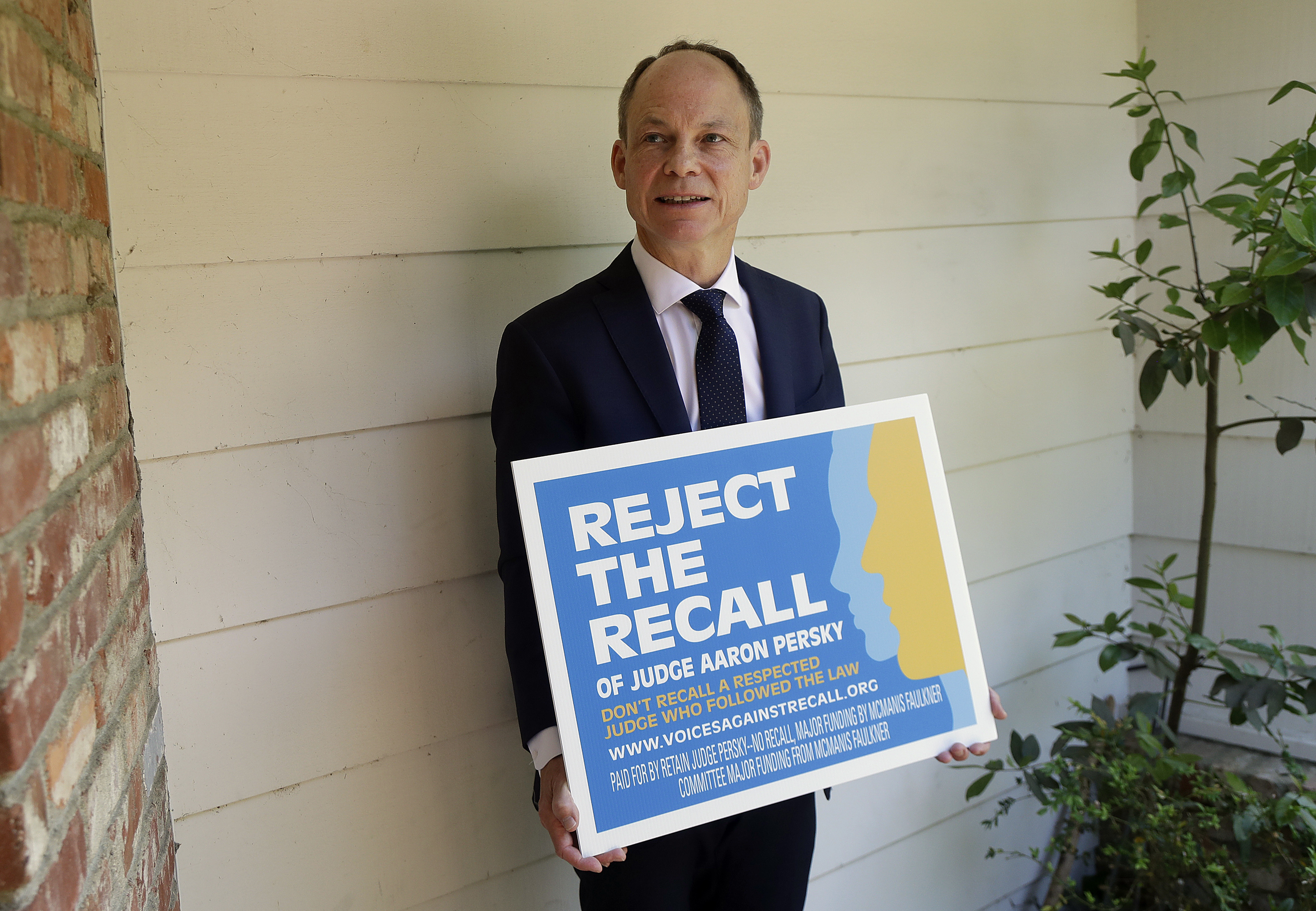 Judge Aaron Persky poses for a photo with a sign opposing his recall in Los Altos Hills, Calif.