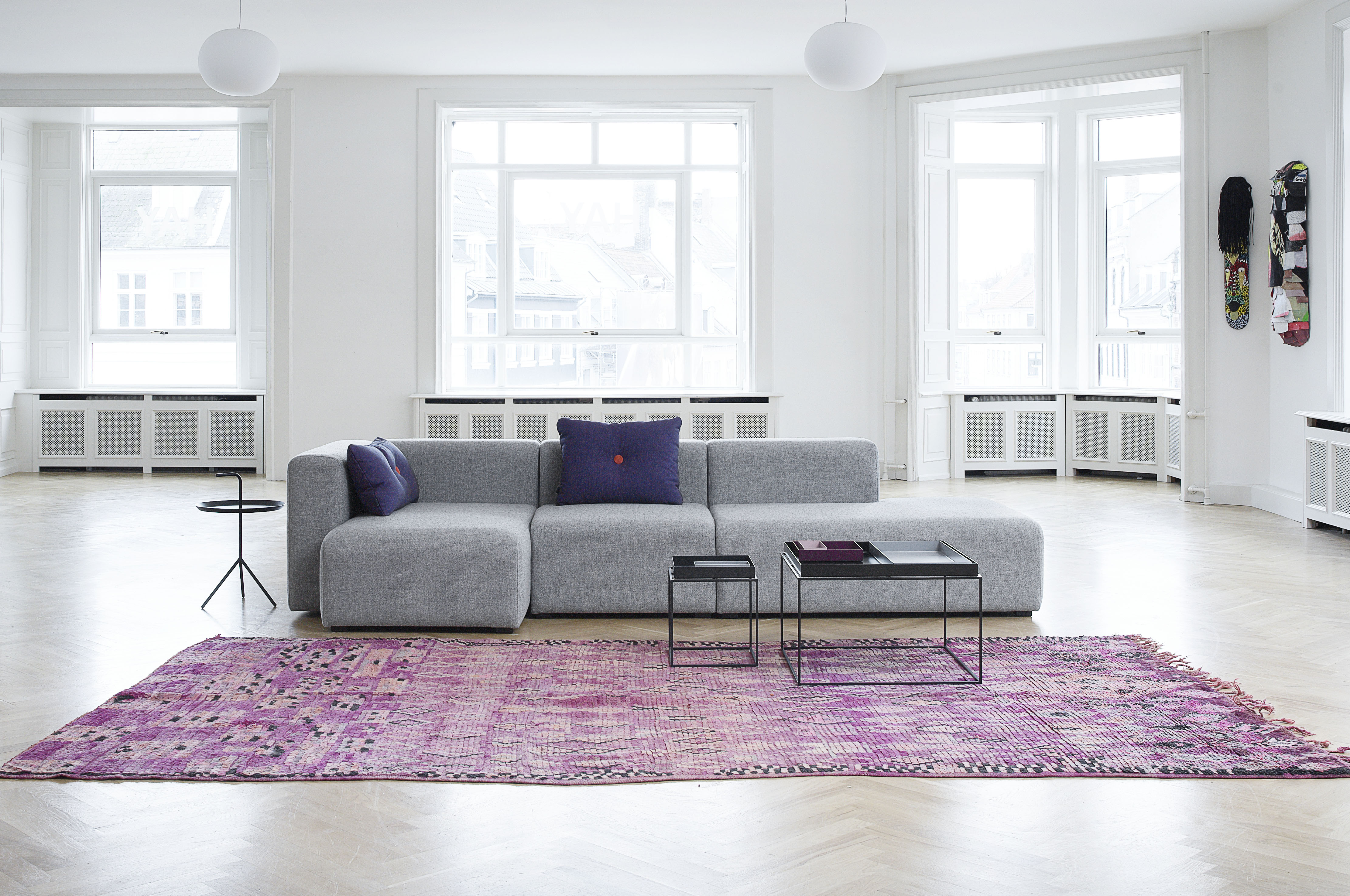Loft space living room scene with sectional couch, rug, and coffee tables.
