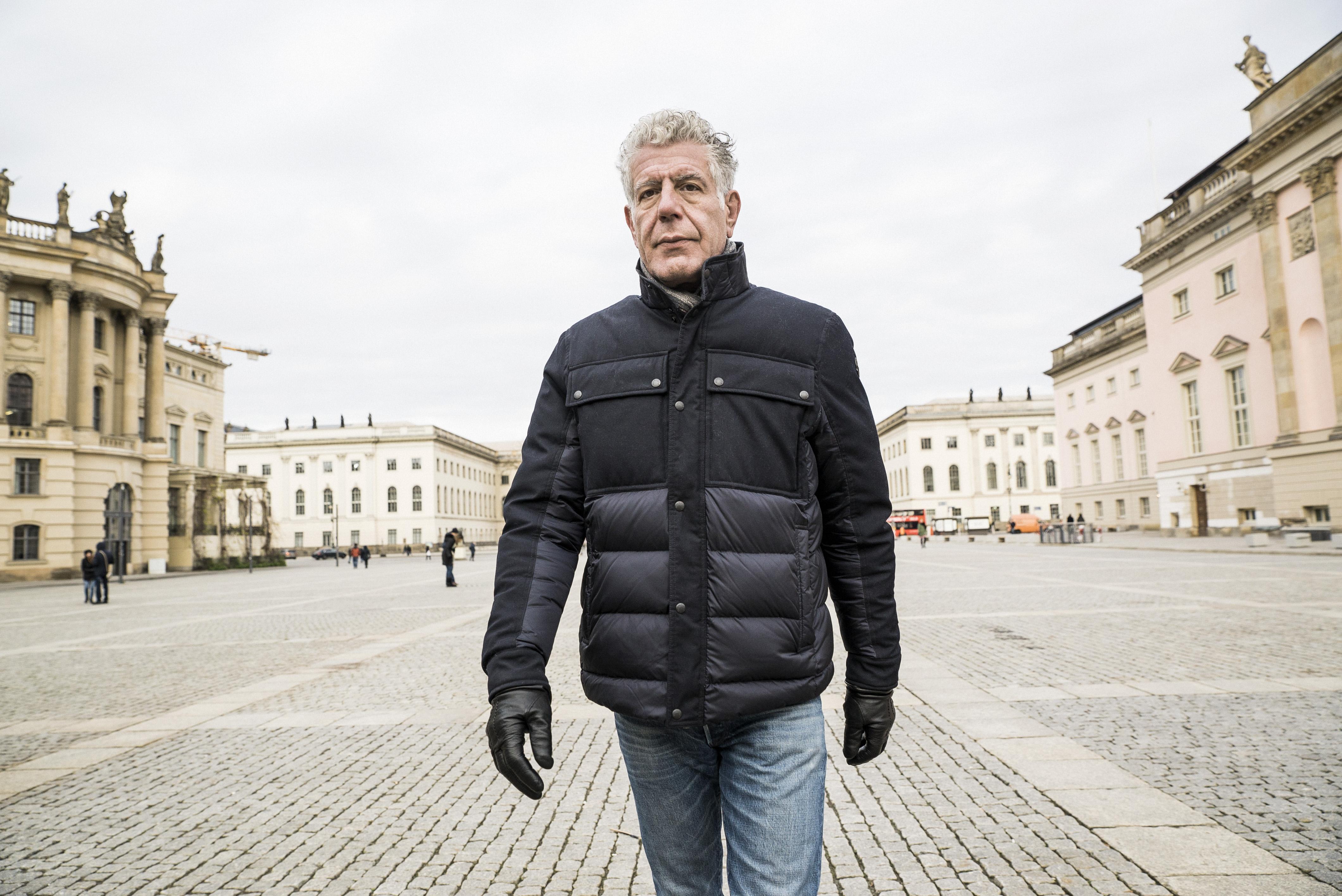 Anthony Bourdain walking through a Berlin square