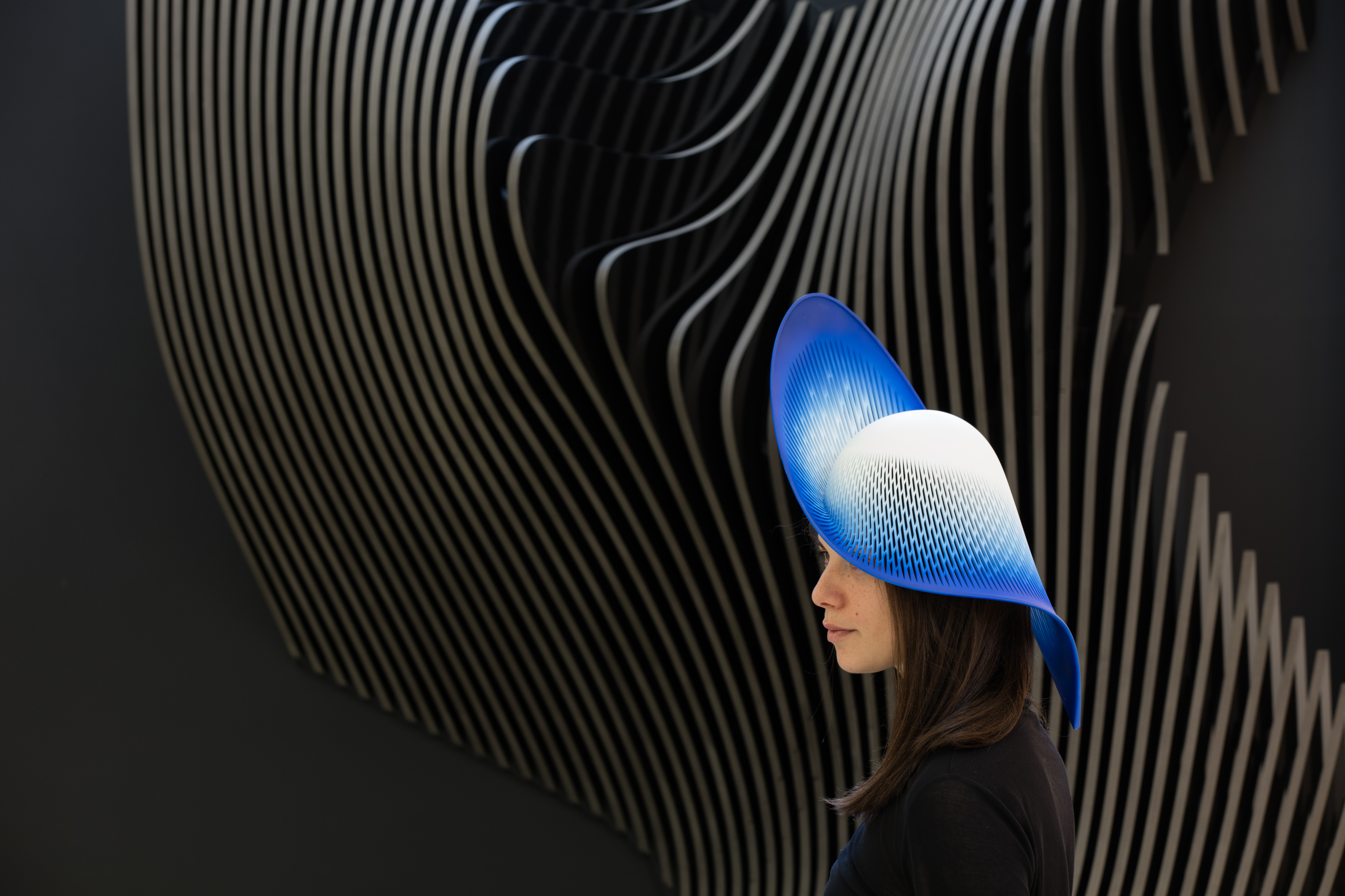 Side profile shot of a woman wearing a molded plastic hat that goes from white to blue with a front brim flipping up and the back one dipping down.