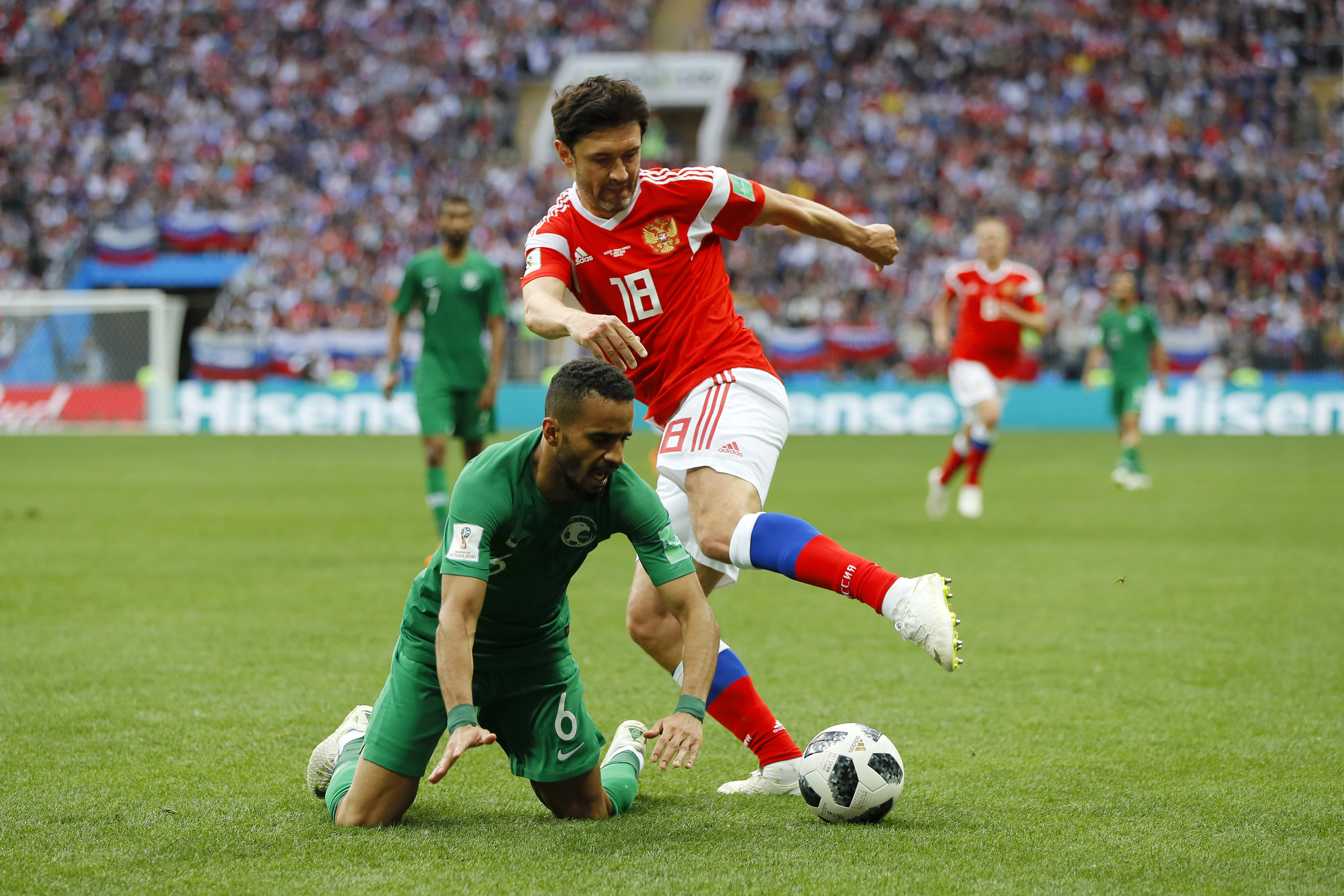 A soccer player in red goes for the ball as a soccer player in green falls to his knees in the opening World Cup soccer match between Saudi Arabia and Russia.
