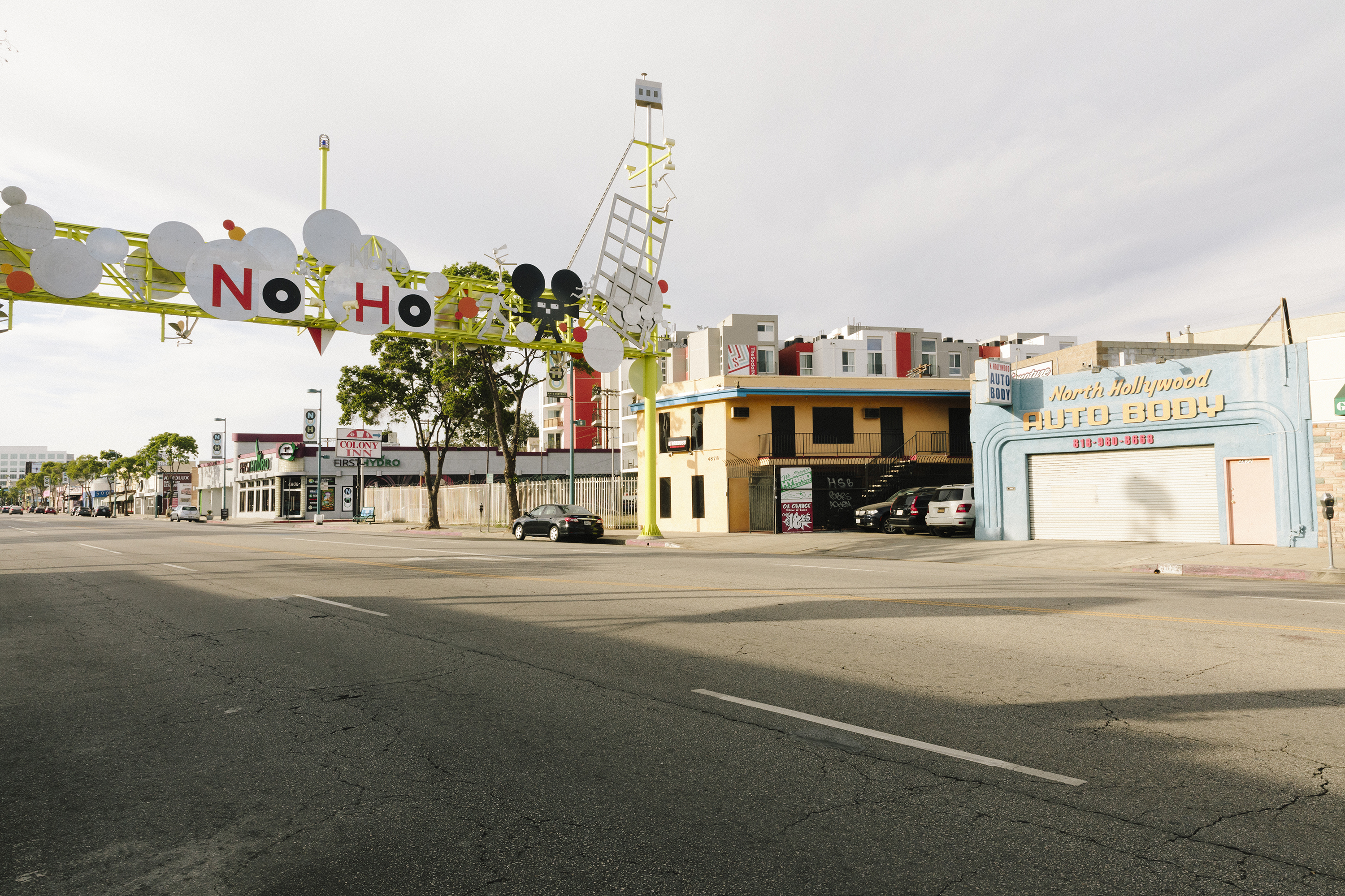 A sign that hangs above the street reads NO HO in red and black letters, on a metal sign that is yellow, white, black and red. On the street is the North Hollywood Auto Body shop, along with various other small buildings and shops.