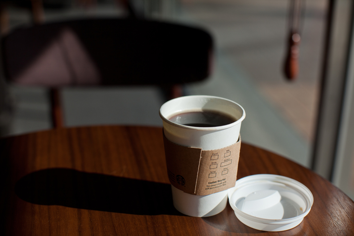 A Starbucks cup full of coffee with the lid removed sits on a table