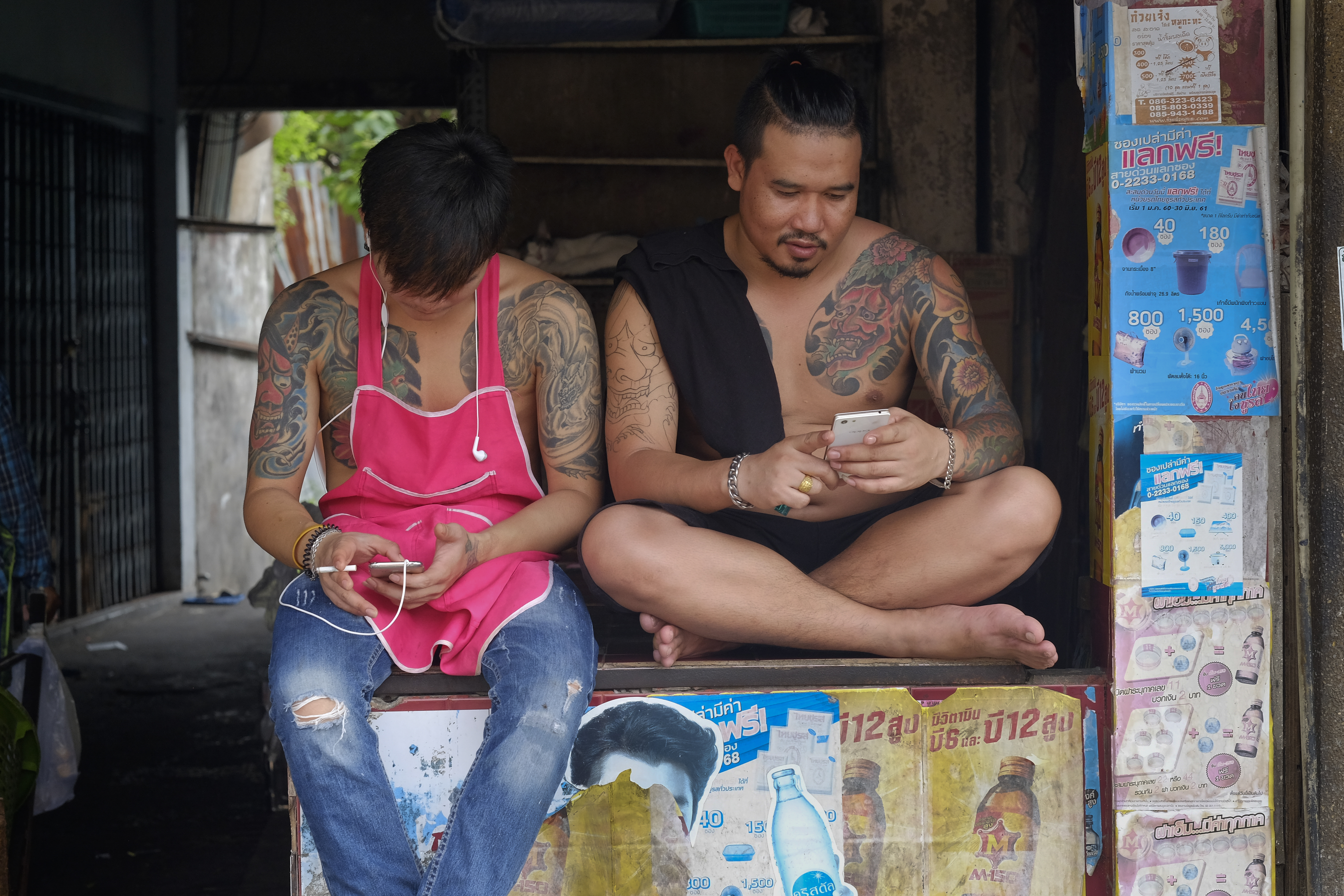 Two heavily tattooed Thai men sit in the back of a truck, each looking at his phone.