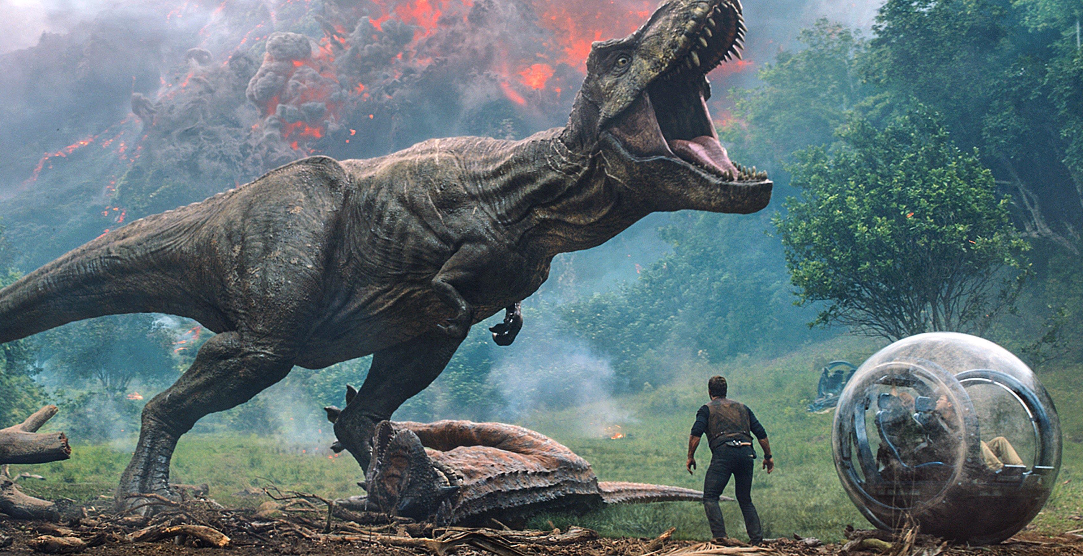 A dinosaur roars at Owen (Chris Pratt) in Jurassic World: Fallen Kingdom.