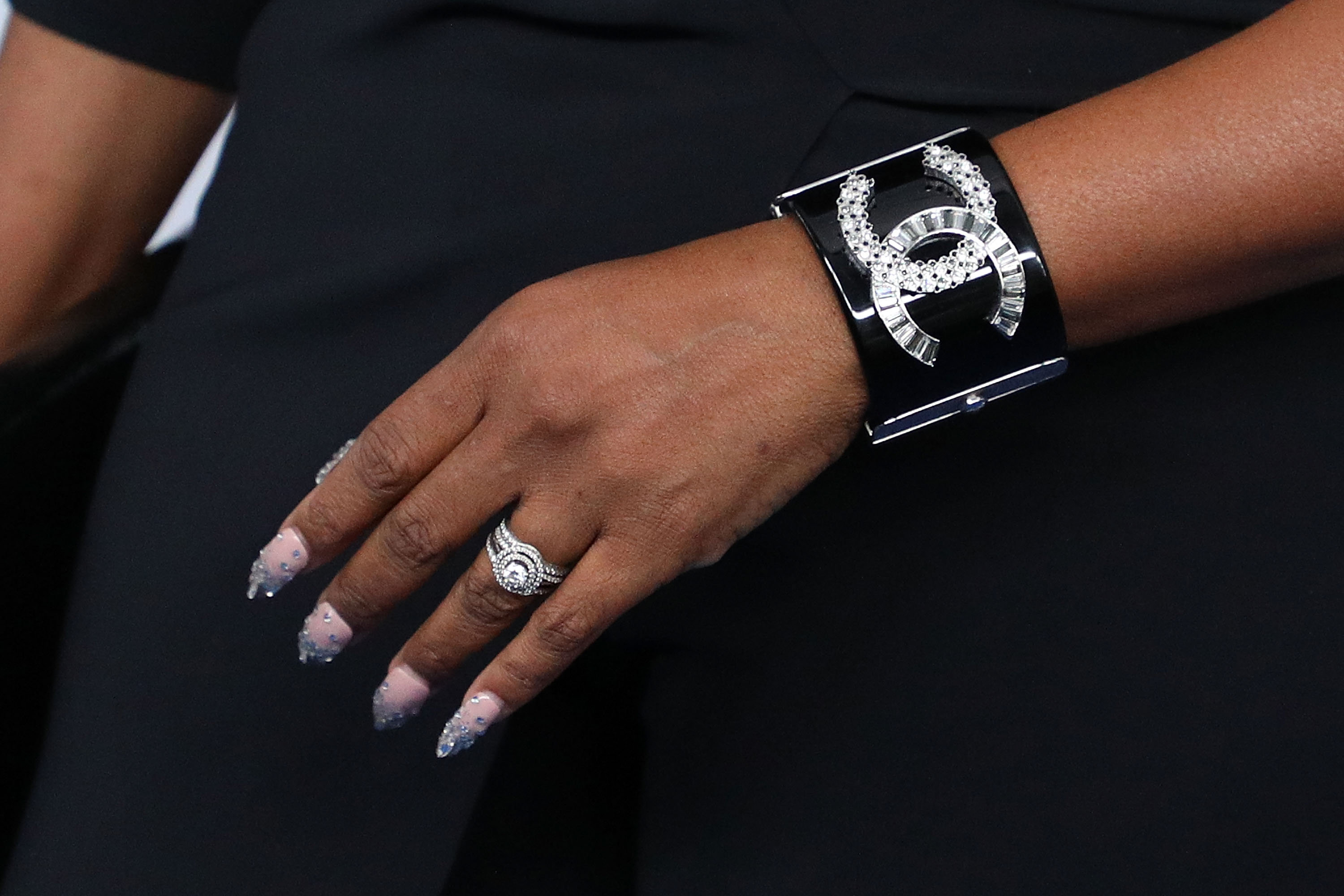 A woman wears a Chanel bracelet.