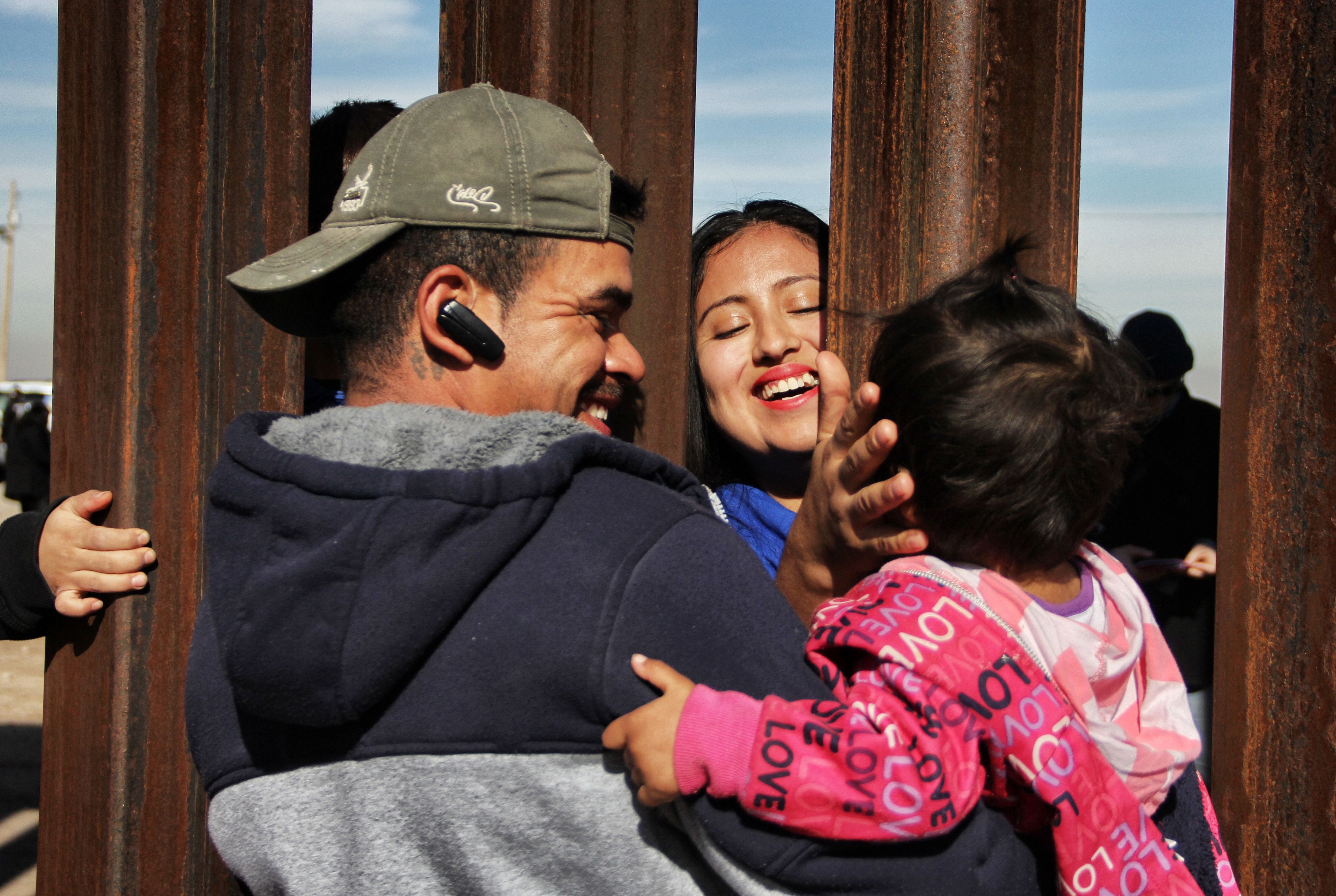 A family reunites at the border wall along El Paso, Texas, and Juarez, Mexico.