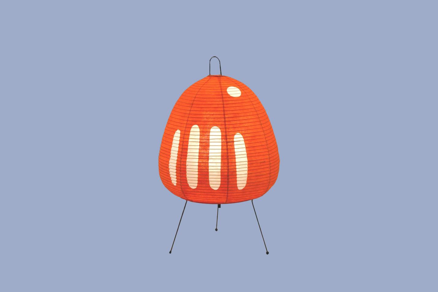 Egg-shaped orange paper lantern with white stips on thin tripod legs.