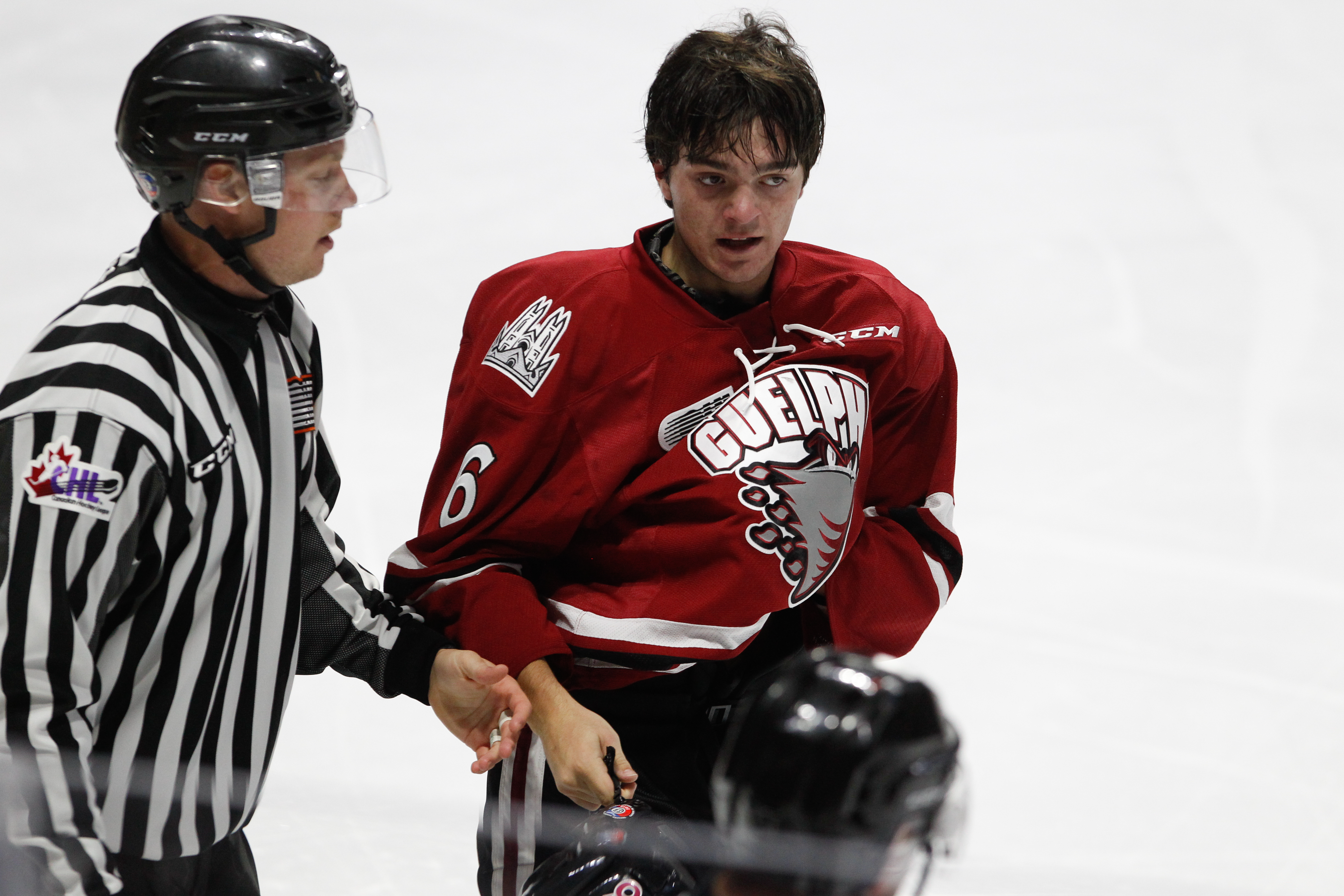 WINDSOR, ON - SEPTEMBER 24: Defenceman Ryan Merkley #6 of the Guelph Storm is escorted to the penalty box during a game against the Windsor Spitfires on September 24, 2017 at the WFCU Centre in Windsor, Ontario, Canada.
