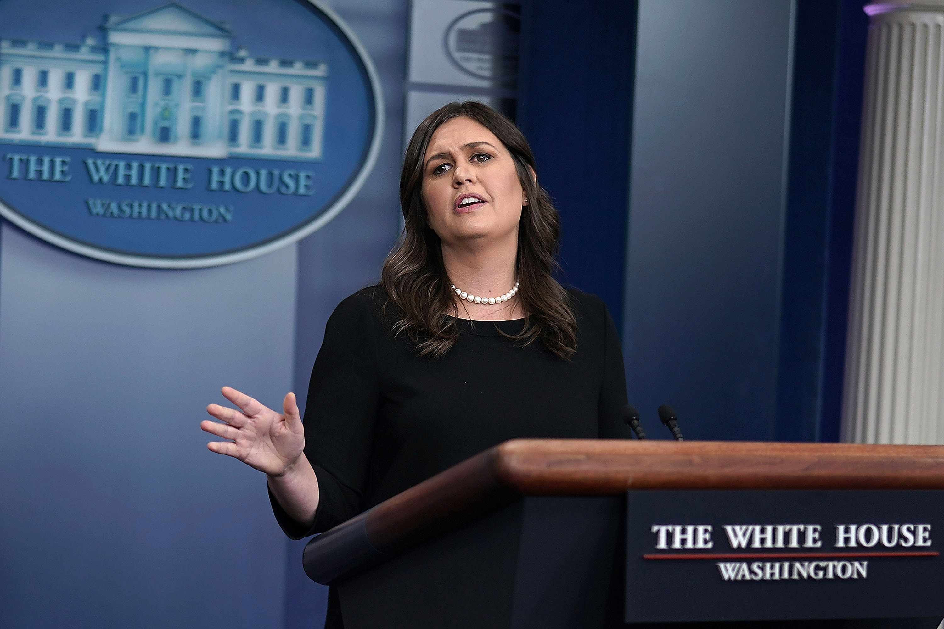 Sarah Sanders stands behind a podium, speaking to reporters.