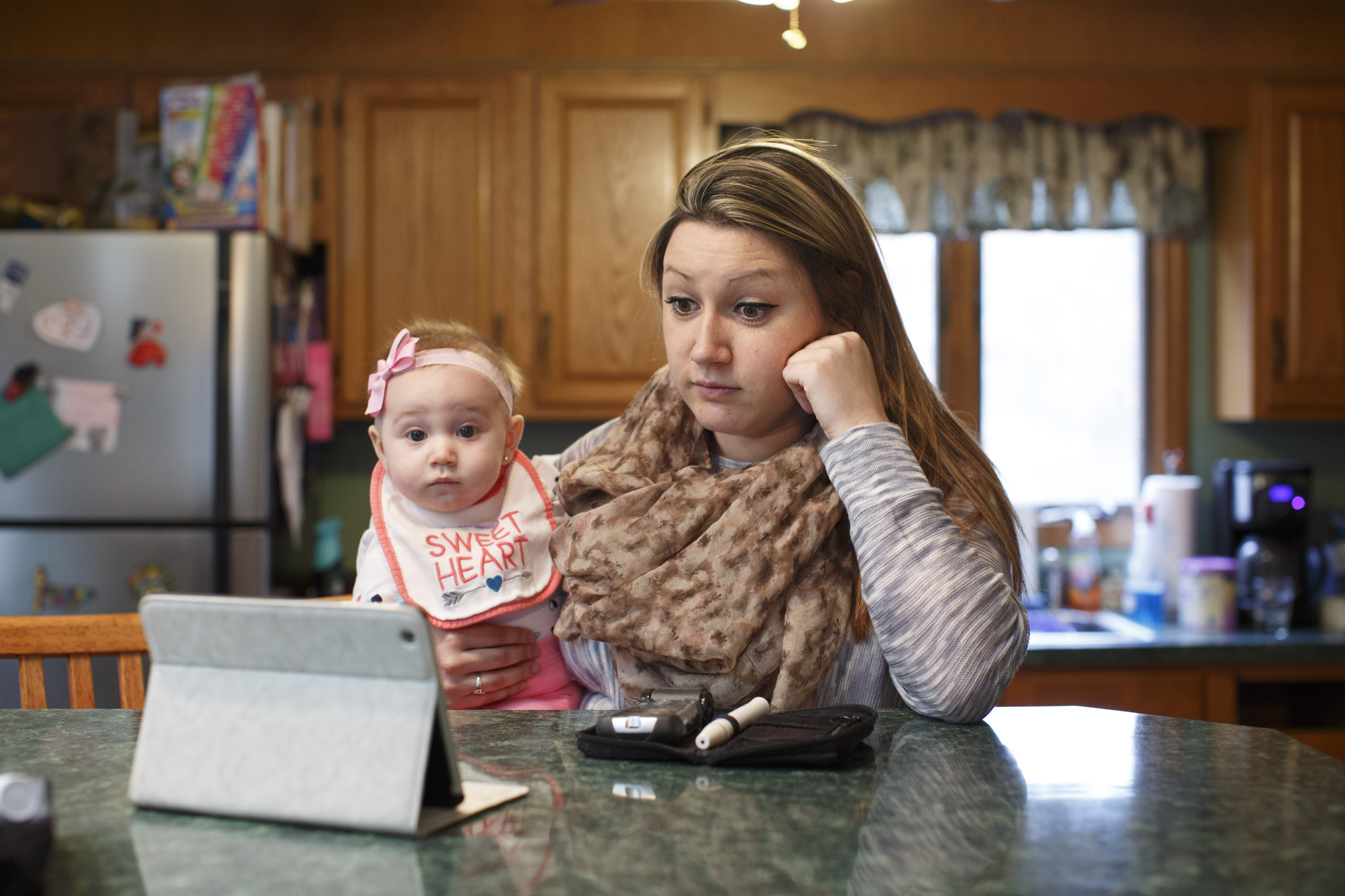 A mother and baby daughter sit in their house looking at a laptop screen.