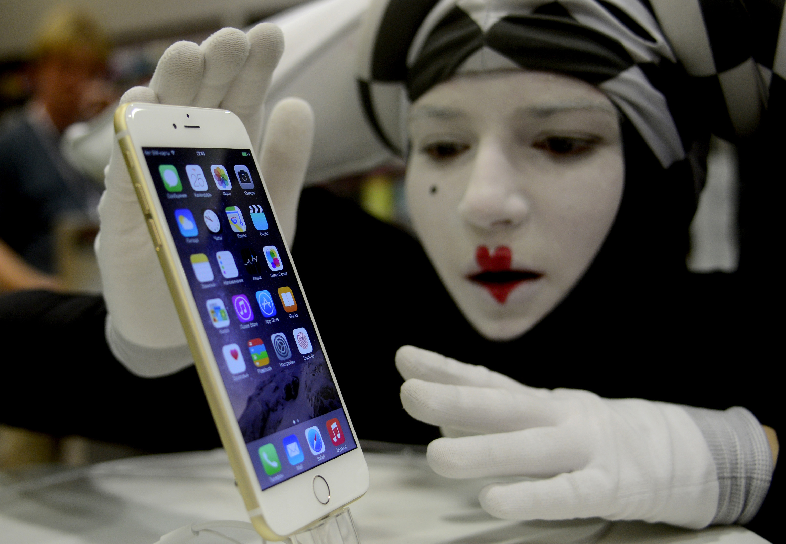 A white-faced mime strokes an iPhone