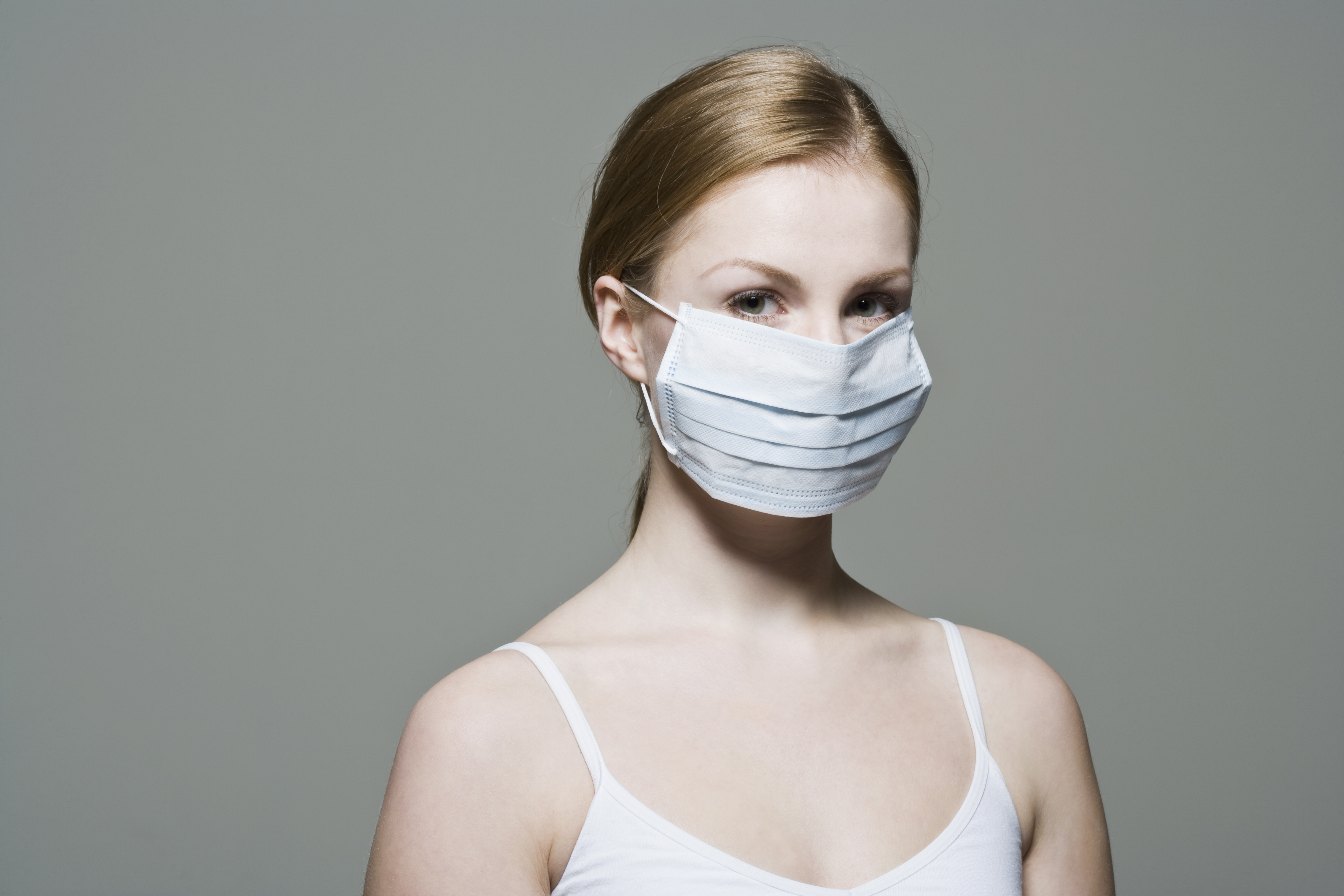 A woman wears a disposable dust mask.