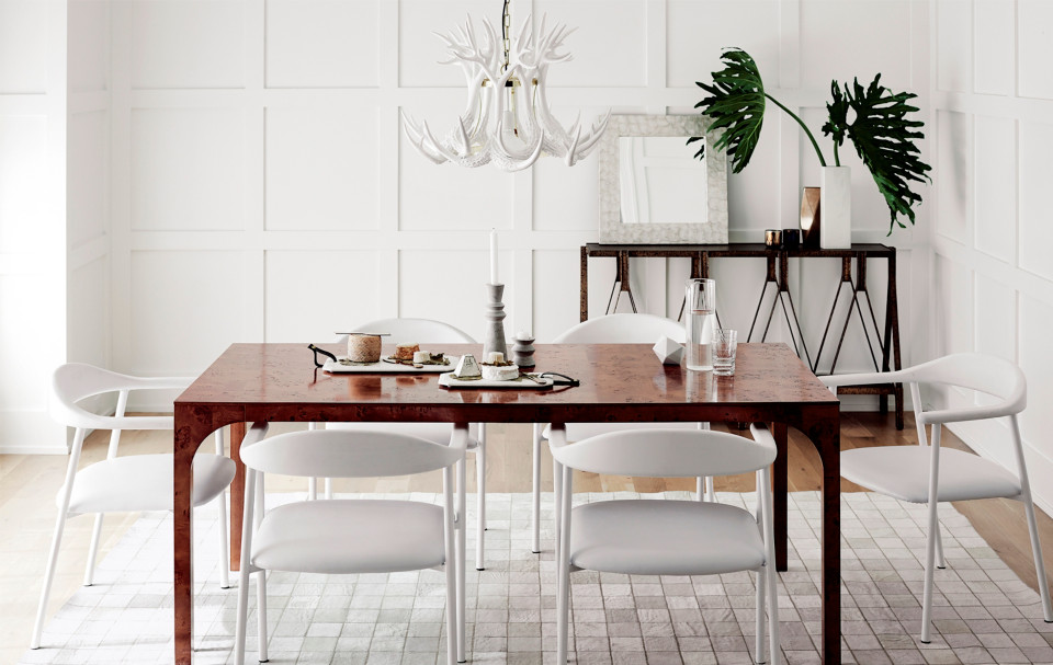 All-white space with a hi-gloss modern dining table and four white chairs.