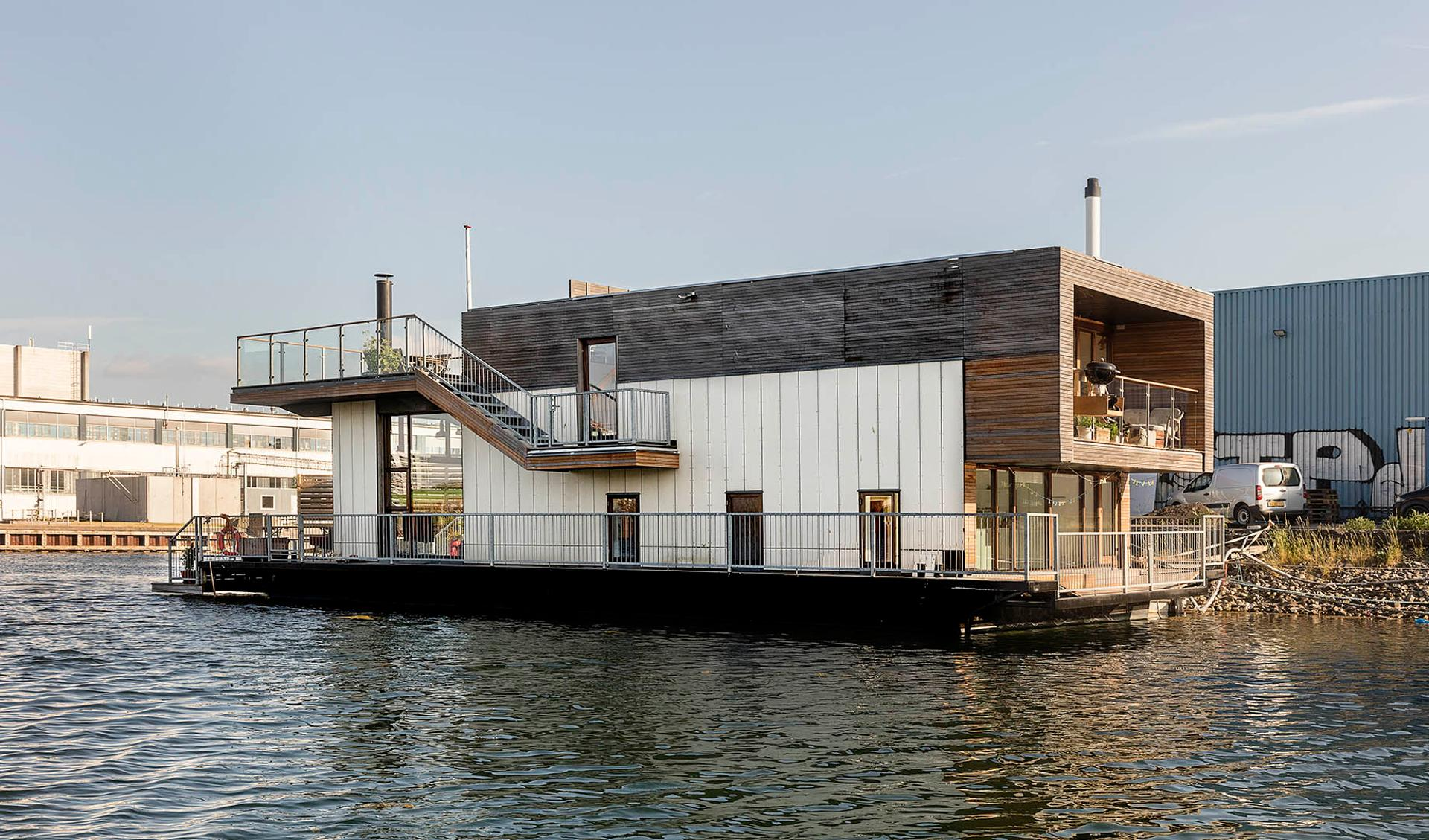 A cubic modern houseboat sits in Copenhagen's Teglholmen harbor, and features plenty of outdoor terrace space in addition to its high-ceilinged living room and two bedrooms. Plenty of high-ceilinged windows allow for sweeping views of the harbor, and outd