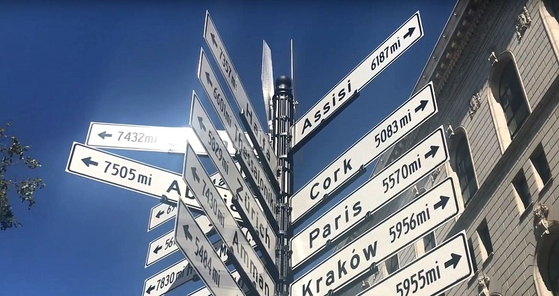 A street sign with the names of various cities pointing in many different directions.