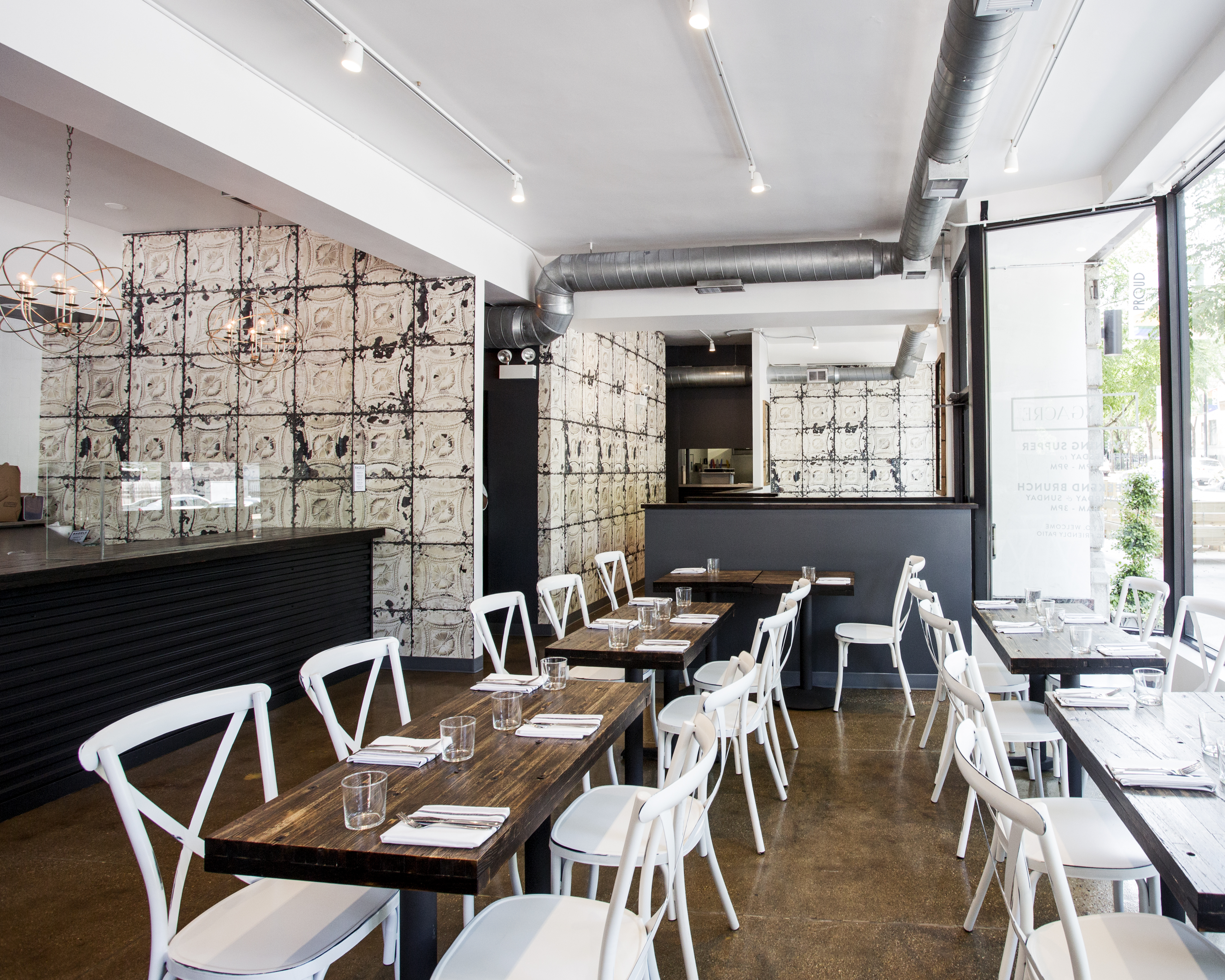 Longacre's dining room is whitewashed with wooden tables with white chairs, white wall tiles, and lots of light.