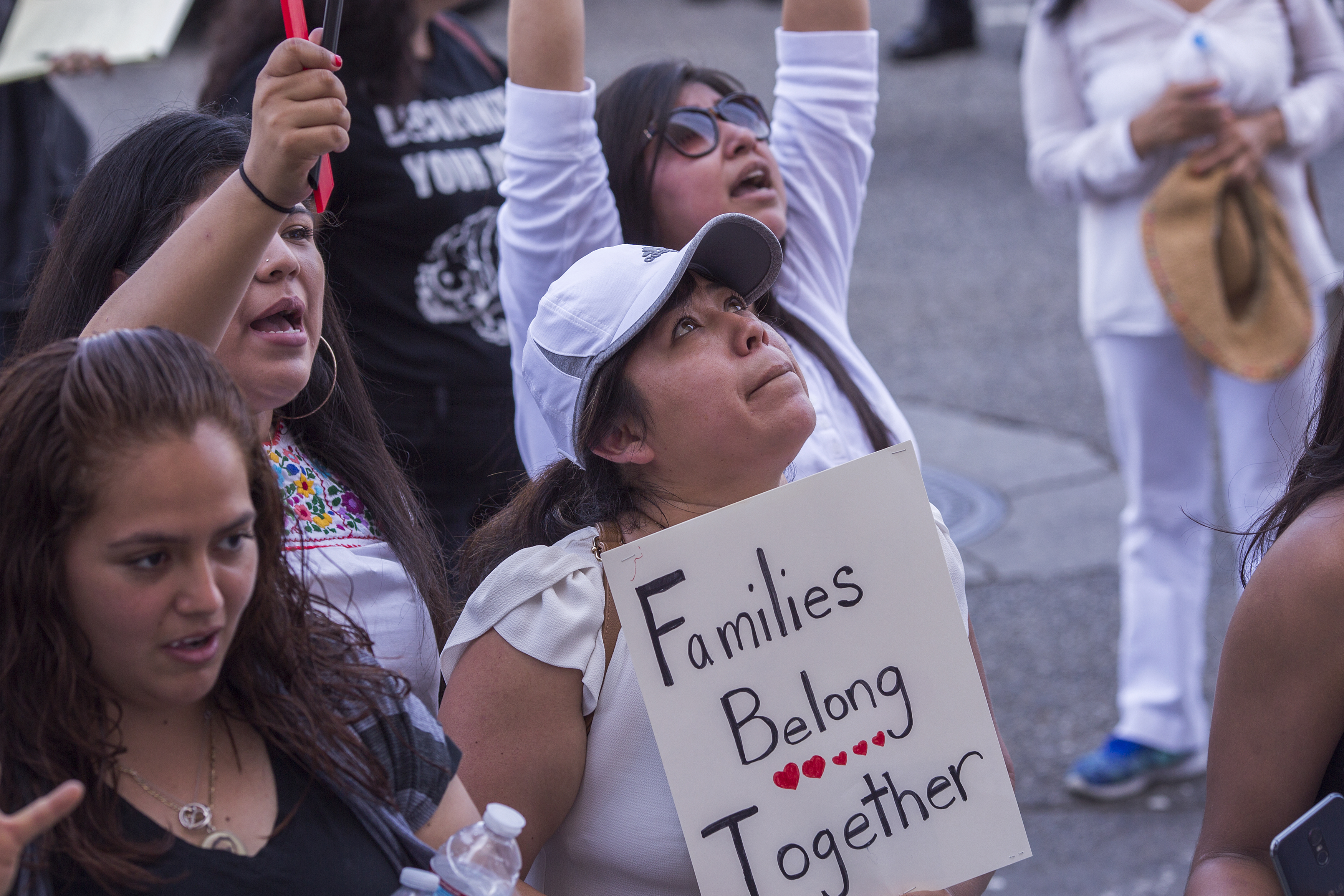 """A protester holds a sign that reads, """"Families Belong Together."""""""