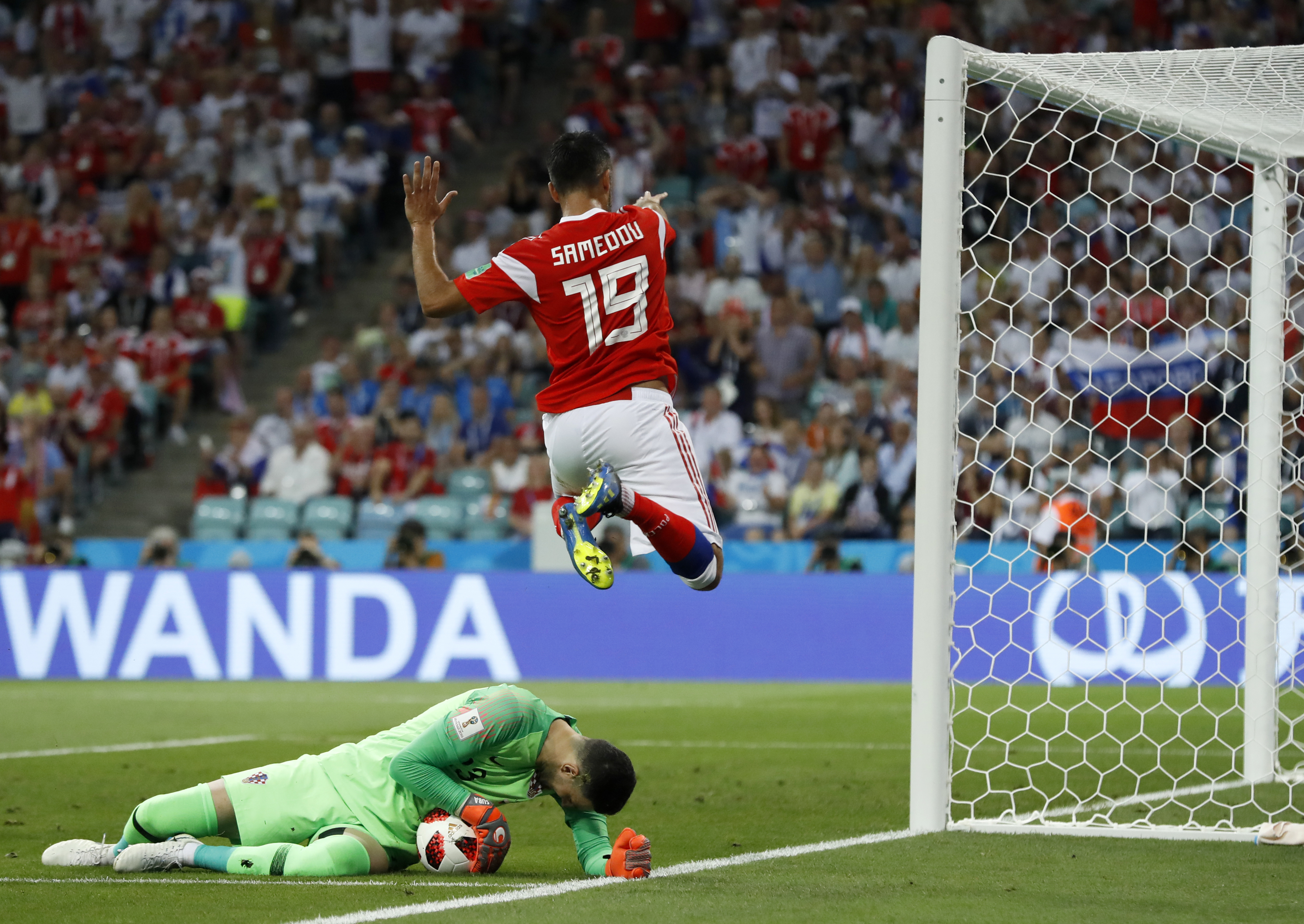 Croatia goalkeeper Danijel Subasic, left, makes a save in front of Russia's Alexander Samedov during the quarterfinal match between Russia and Croatia.