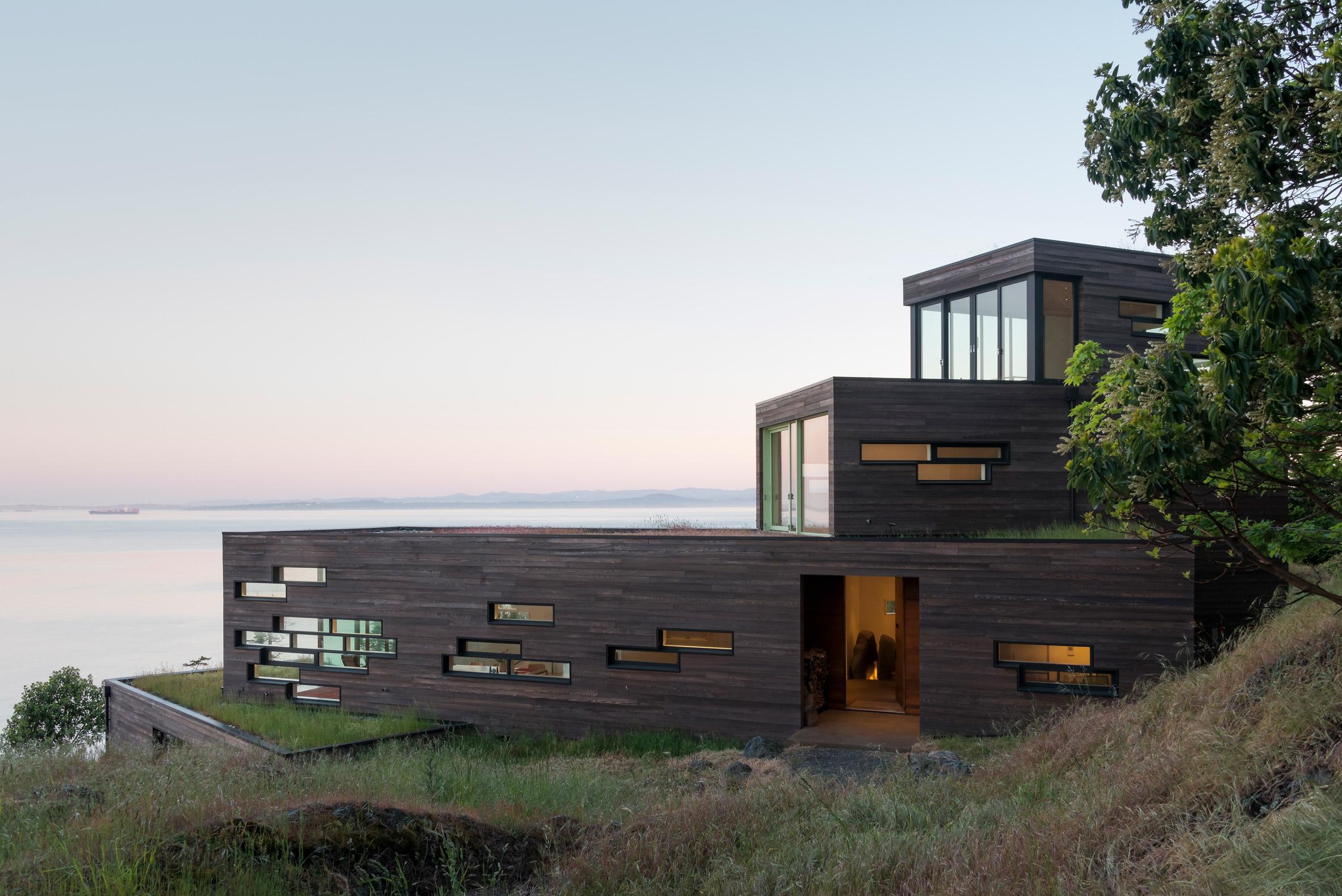 Oceanfront modern house cascades down a rocky hill