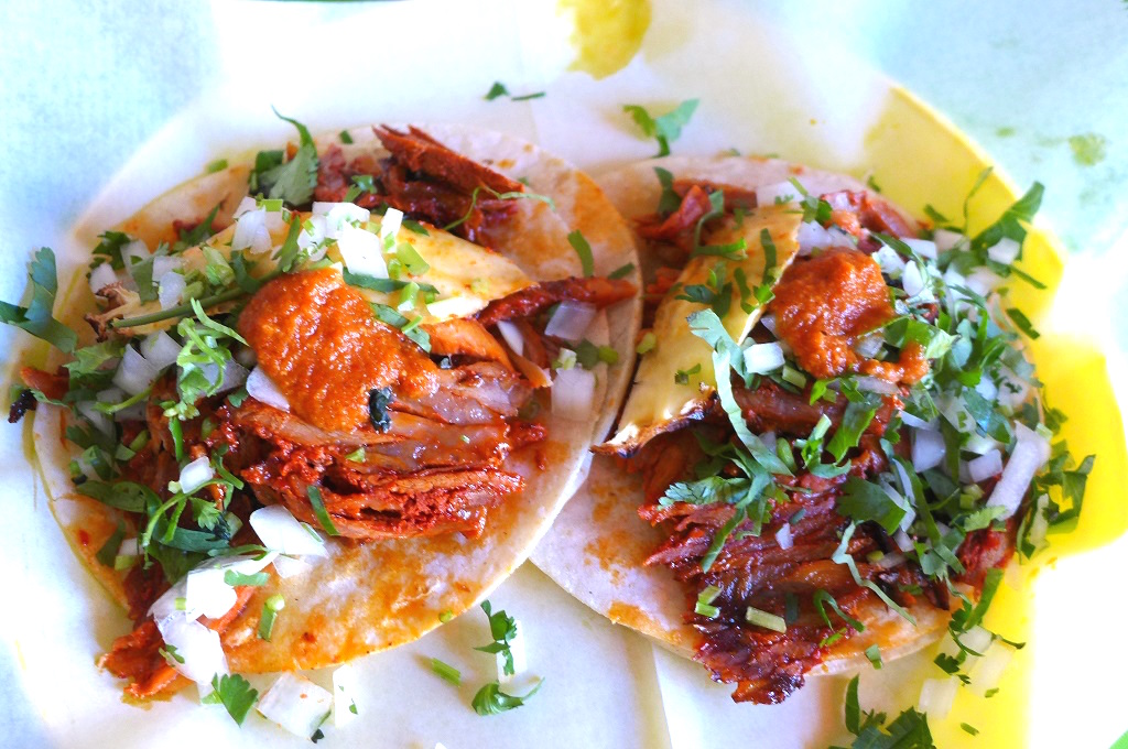 Two al pastor tacos side by side