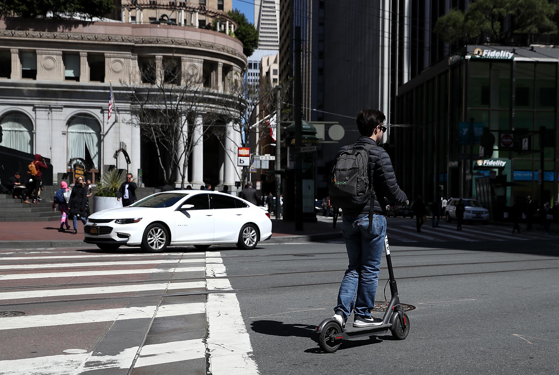 A person rides an electric scooter through a San Francisco intersection.