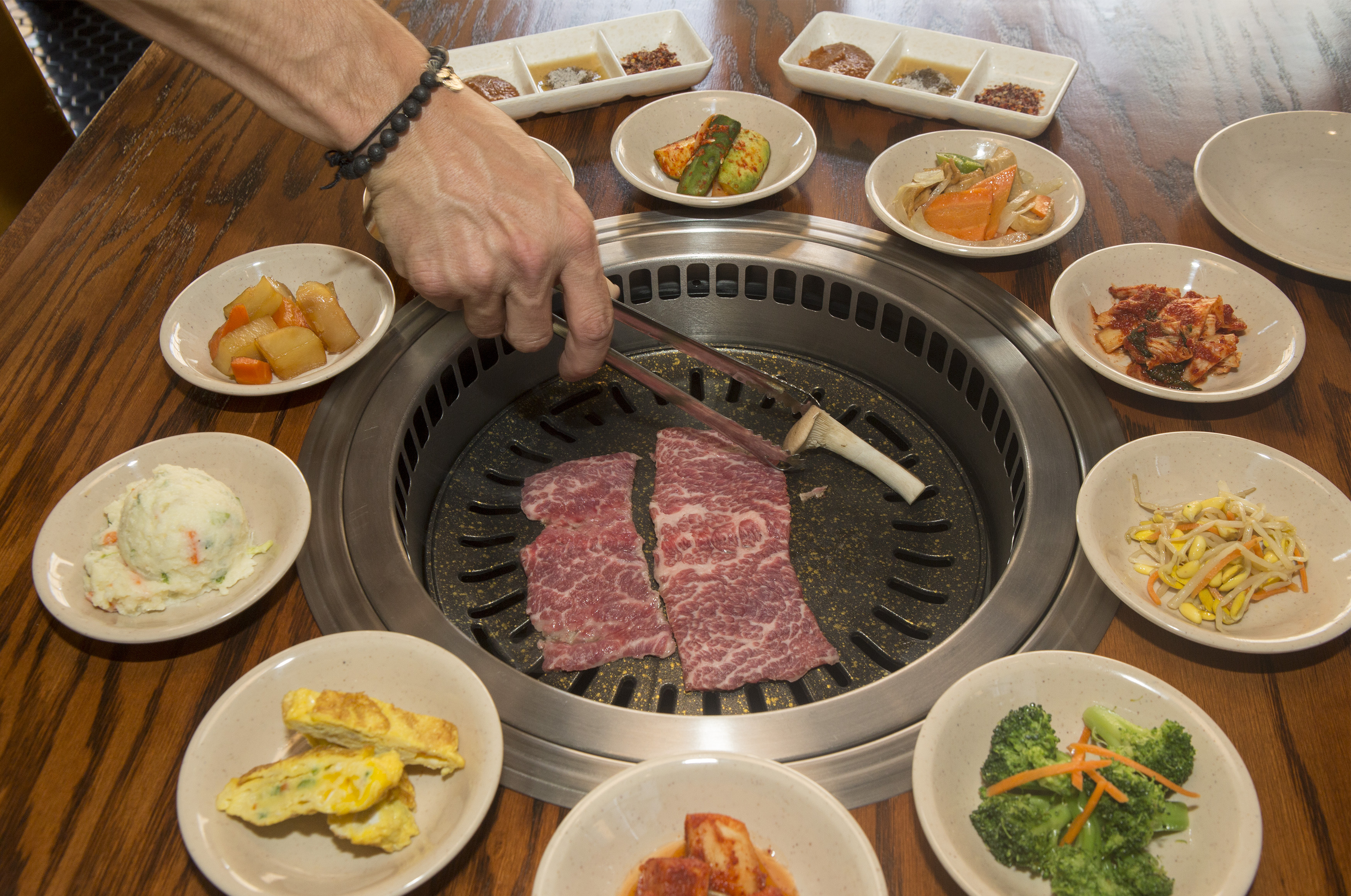 A person grilling meat on a tabletop grill that's surrounded by banchan.