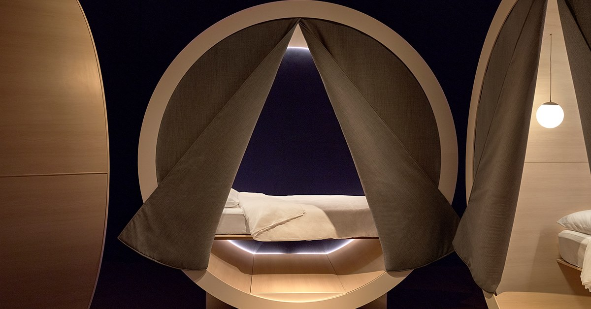 A circular wooden pod with a bed inside.
