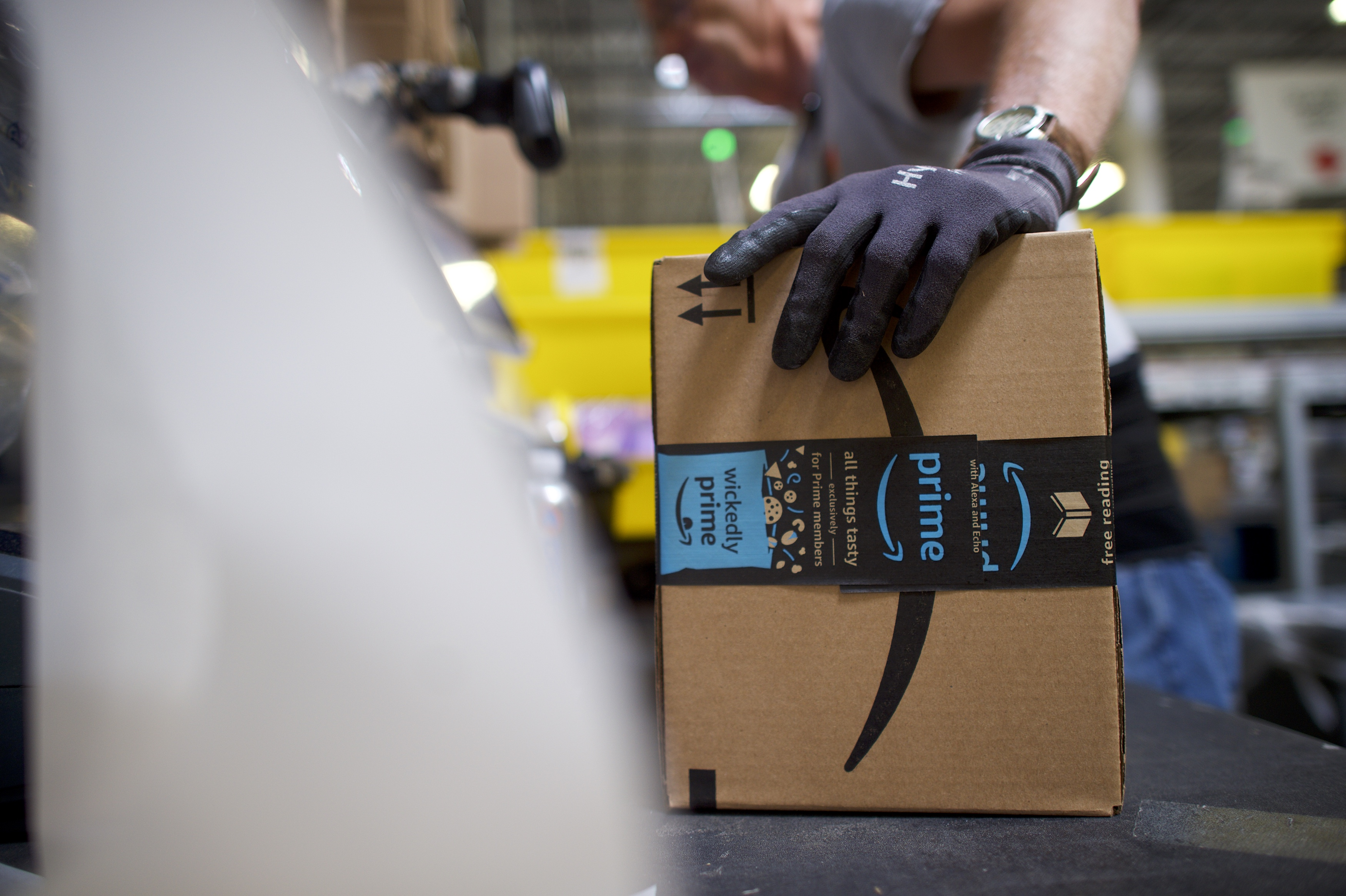 A worker holds a box with an Amazon Prime Day logo.