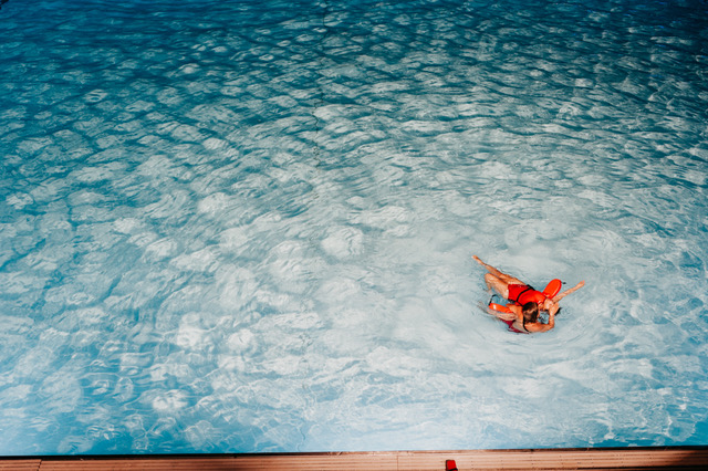 person holding another person floating in a shallow pool with lifeguard floats