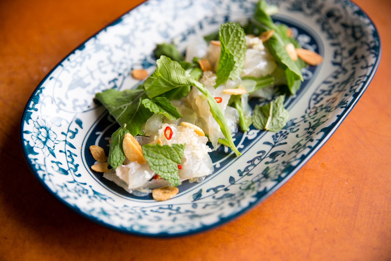 Pla Chae Nahm Pla with madai sashimi, finger limes, mint, fried garlic, arugula, and Thai chiles