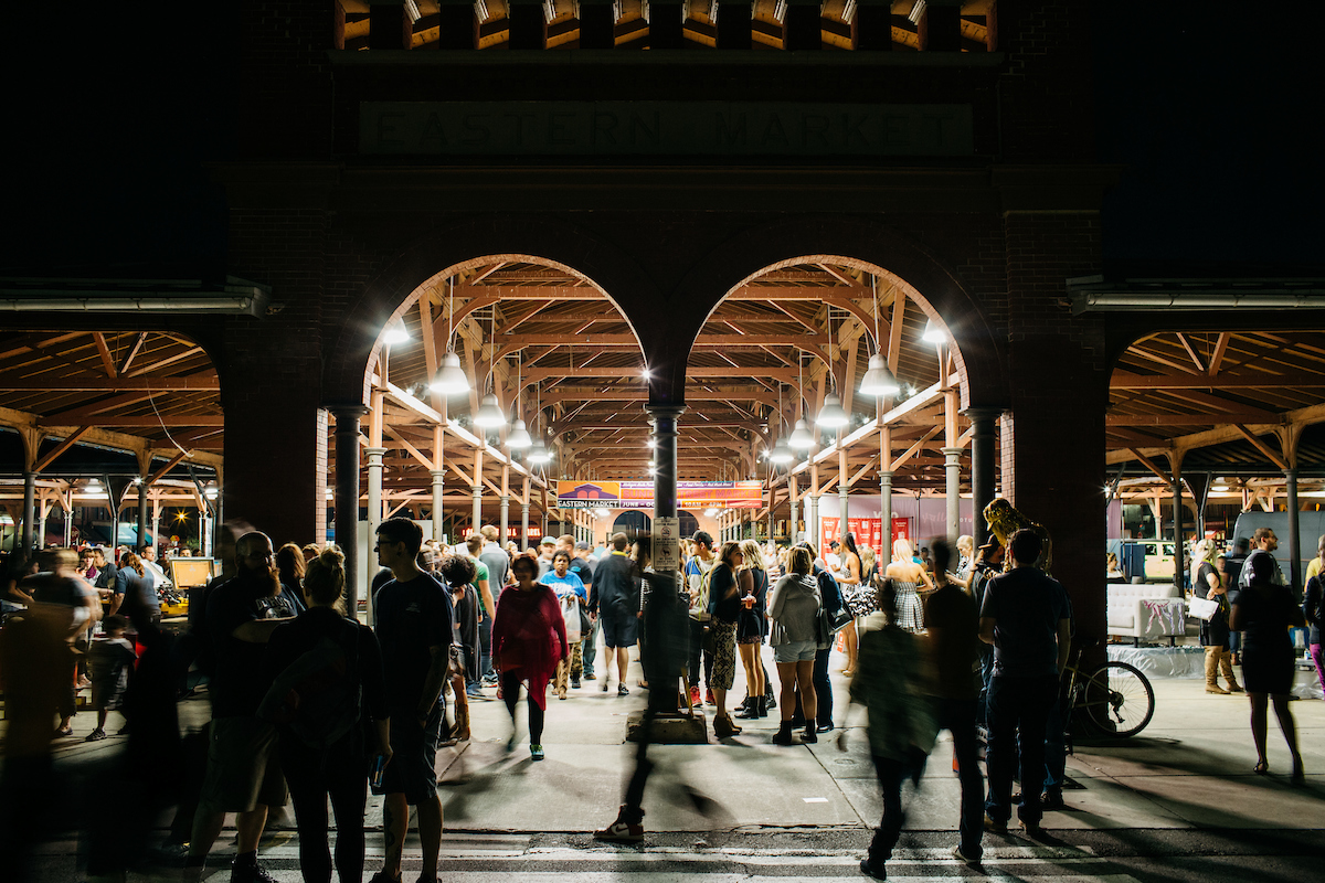 The interior of Eastern Market in Detroit. There is an arched doorway. There are many people standing near market stalls. The ceiling is exposed wooden beams.