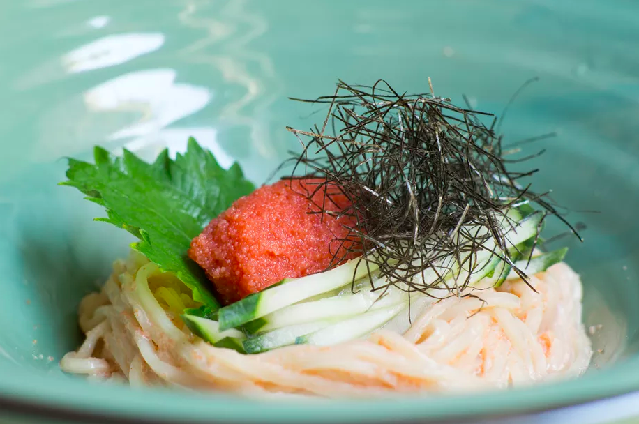 Closeup of a teal-colored ceramic bowl full of udon, topped with sliced cucumber, black seaweed, a shiso leaf, and a red scoop of caviar