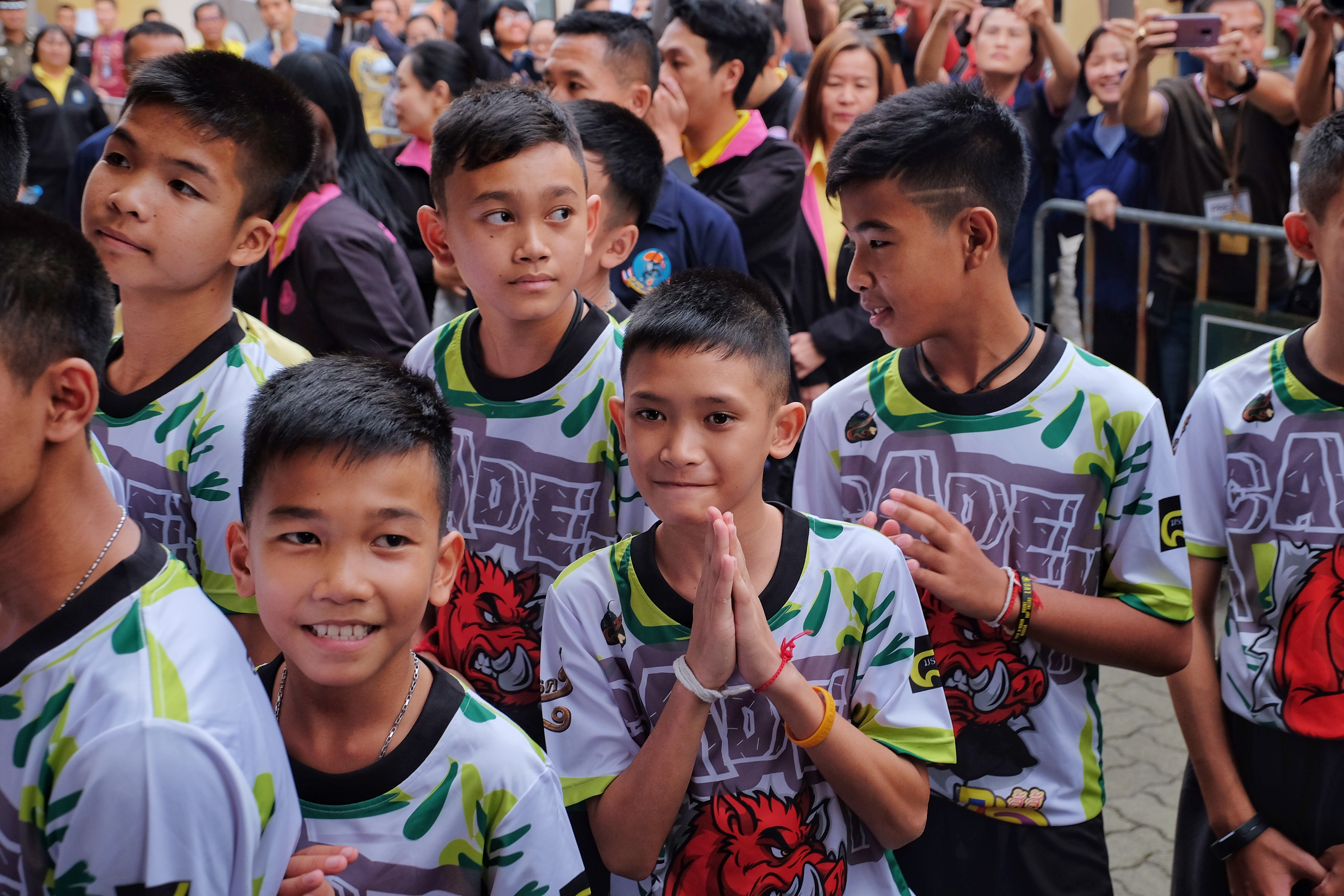 Twelve boys and their coach from the Wild Boars soccer team arrive for a press conference for the first time since they were rescued from a cave in northern Thailand last week.