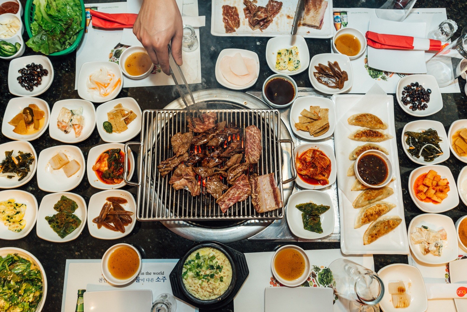 A person grilling meat on a tabletop grill that's surrounded by side dishes.