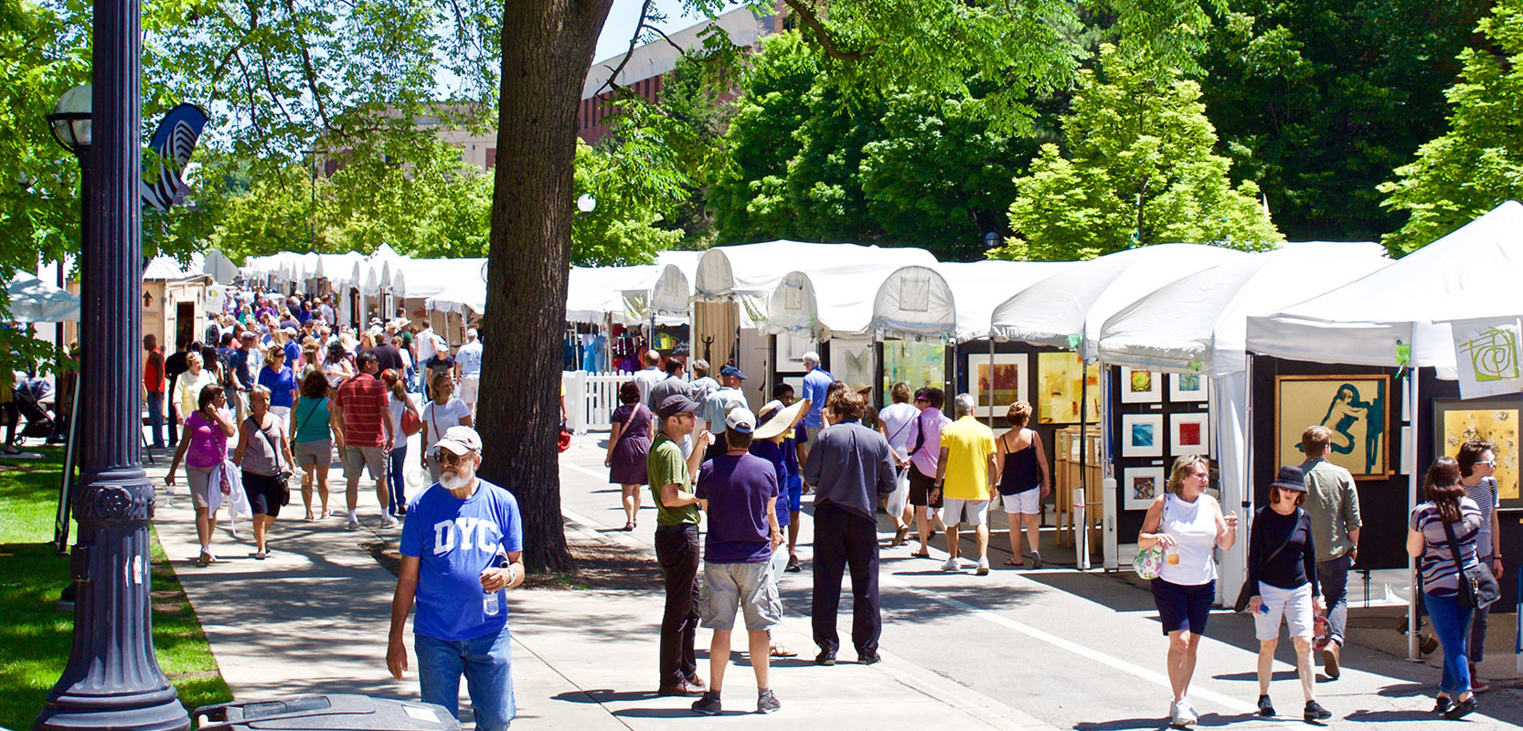 dozens of people walk around the ann arbor art fair's white tented booths