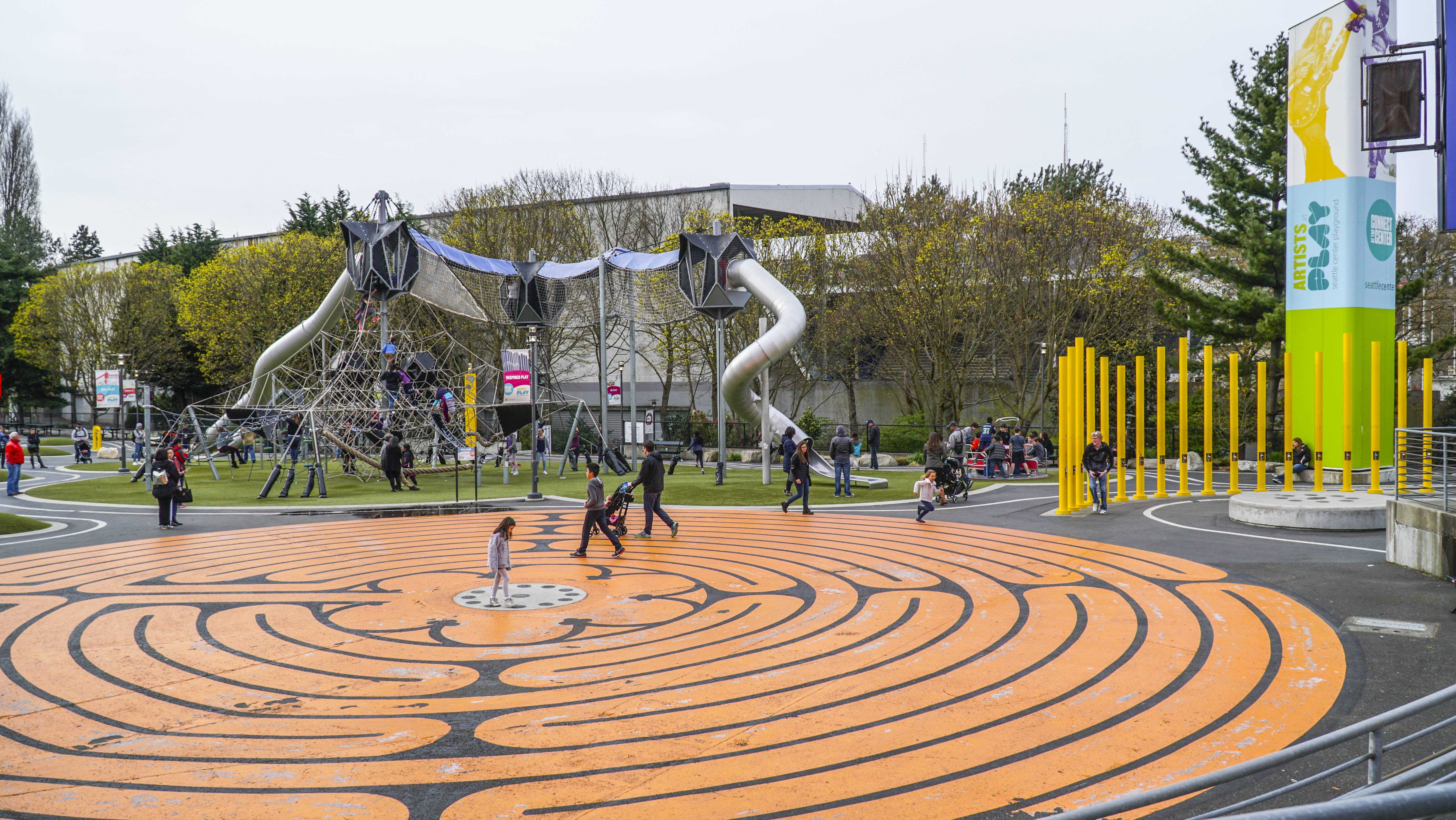A playground with children playing. On the ground in the foreground is an orange circular design. In the distance is various assorted playground equipment.