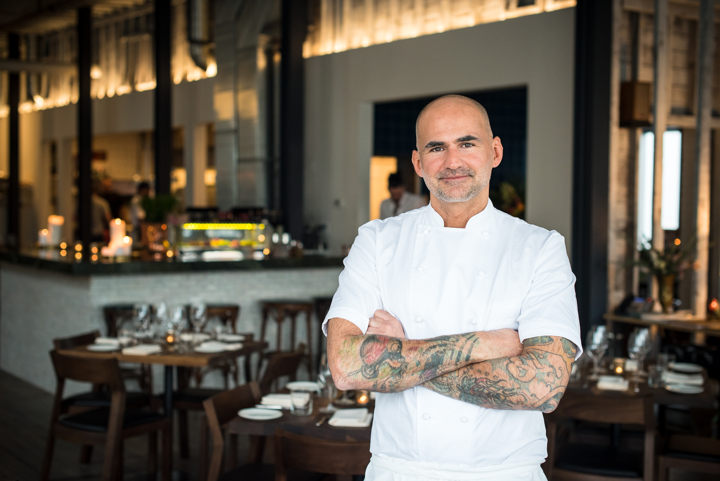 The bald, tattooed chef with a salt and pepper goatee stands, arms crossed, inside a dining room with wood tables and white walls