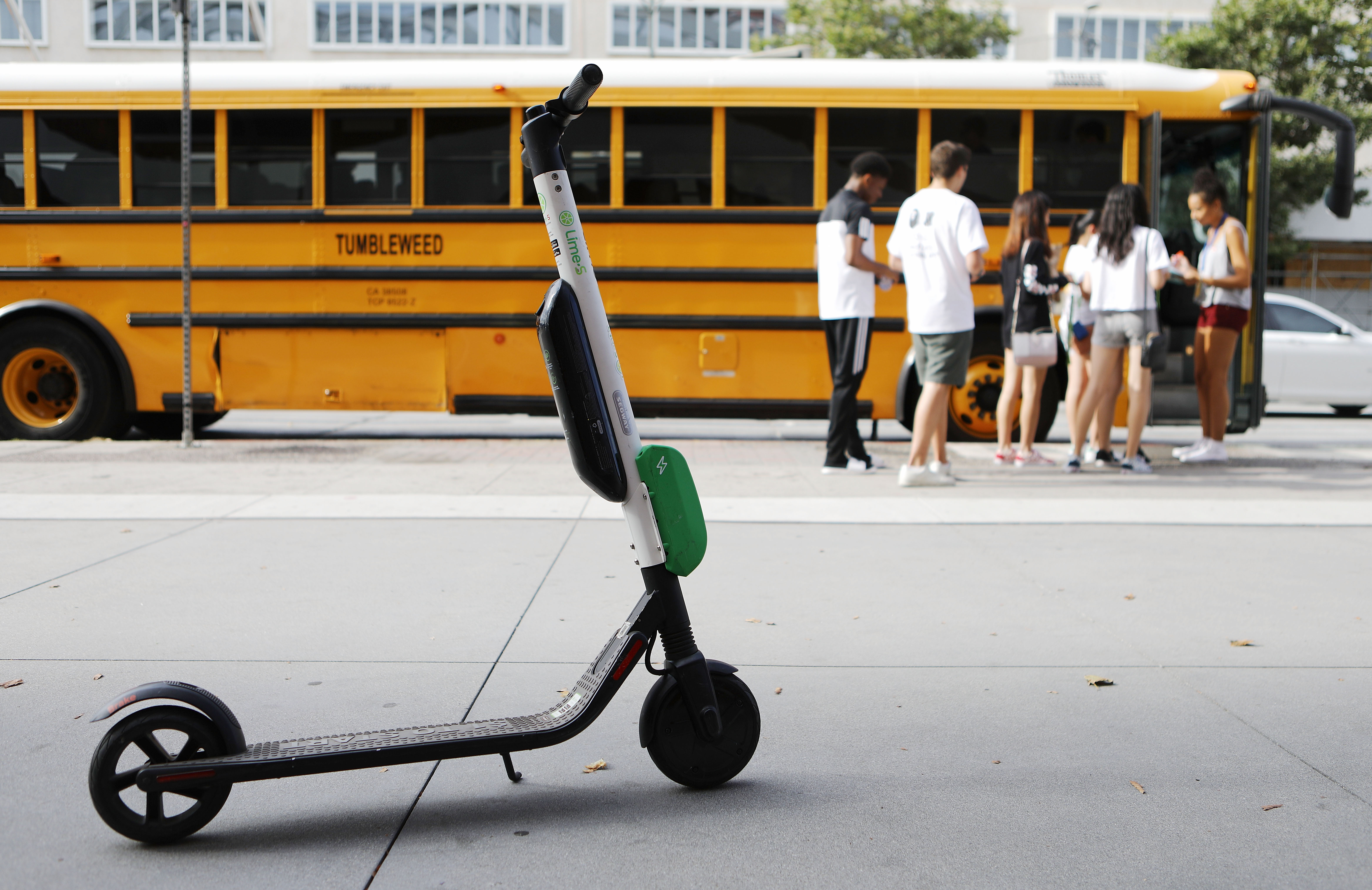An electric scooter parked beside a school bus.