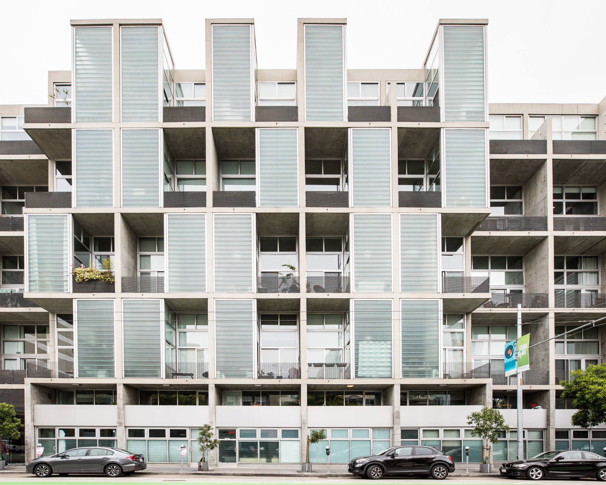 Multiple units on a condo complex with frosted glass blocks galore, and balconies with plants and bikes.