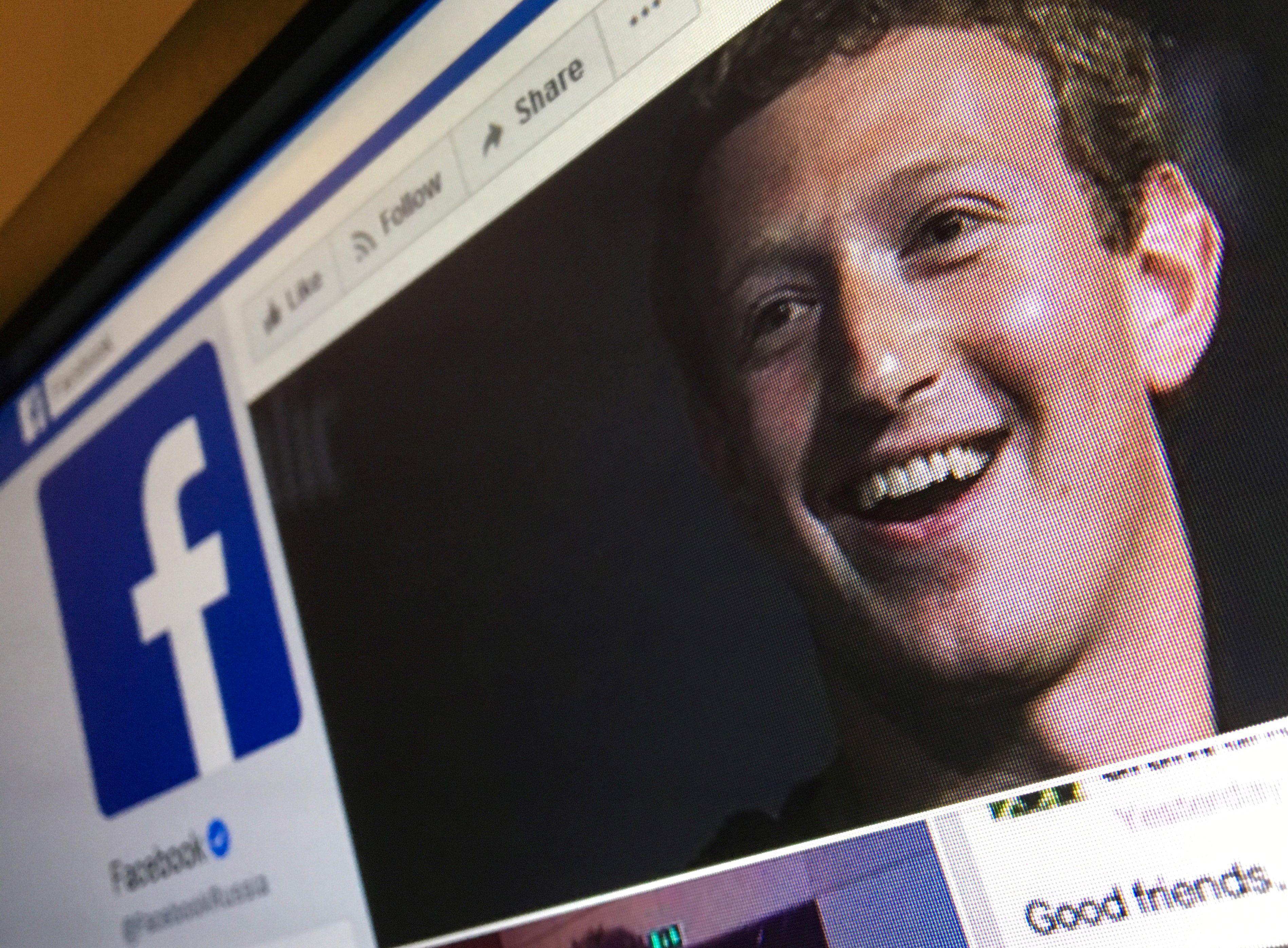 Facebook CEO Mark Zuckerberg on a computer screen with the Facebook logo.