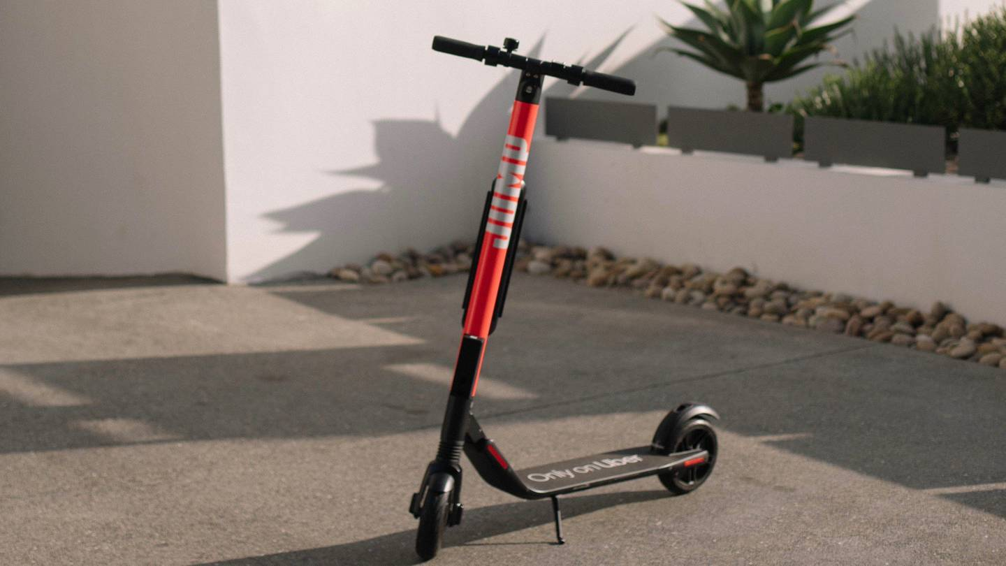 A scooter sits in a driveway. It is black and red.