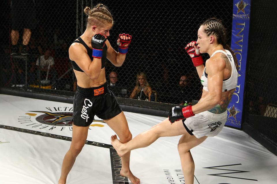 A woman wearing white shorts and top leg kicks a woman in black shorts and top.